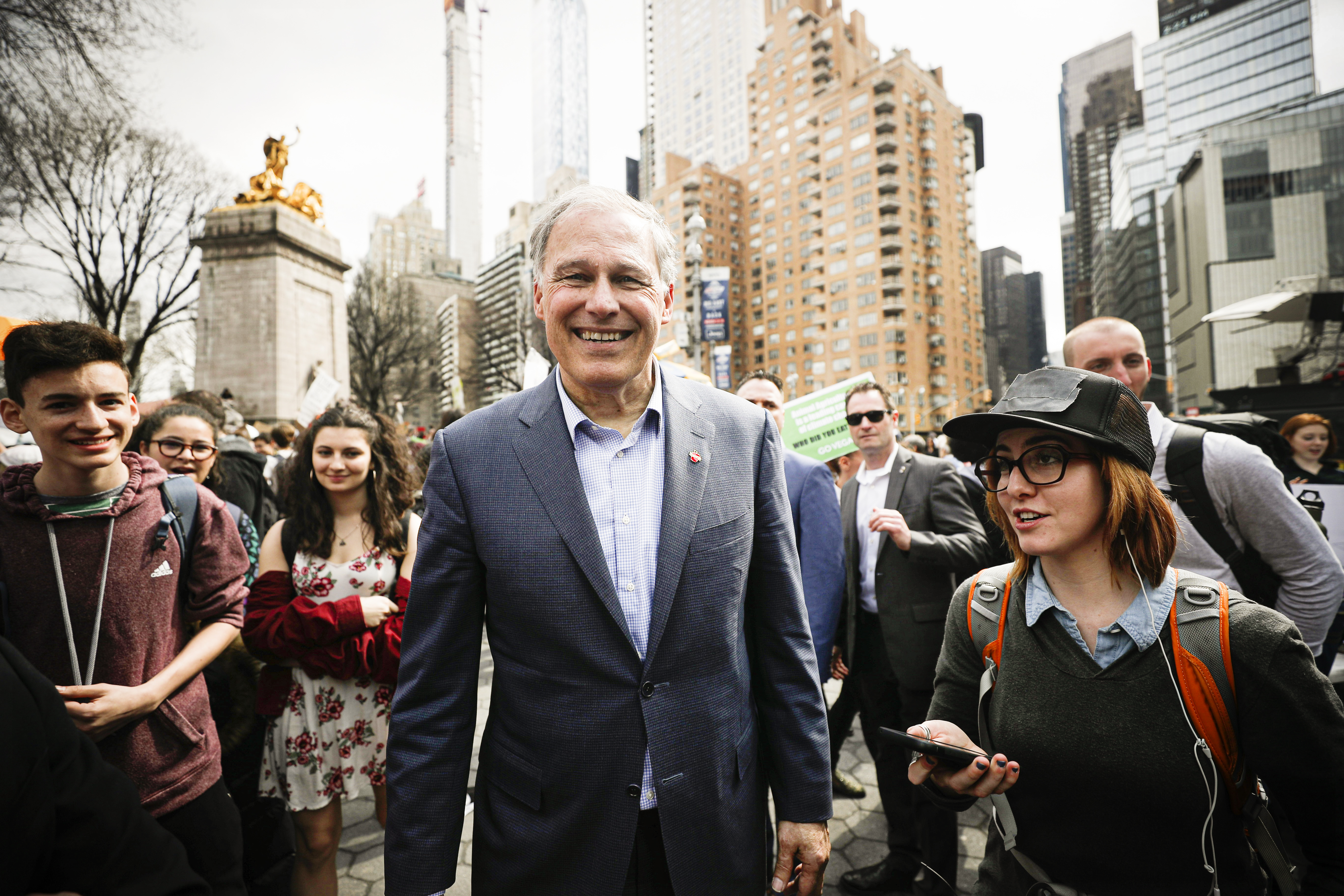 Former Democratic presidential candidate Washington Governor Jay Inslee walking with a group of students down a New York City street.