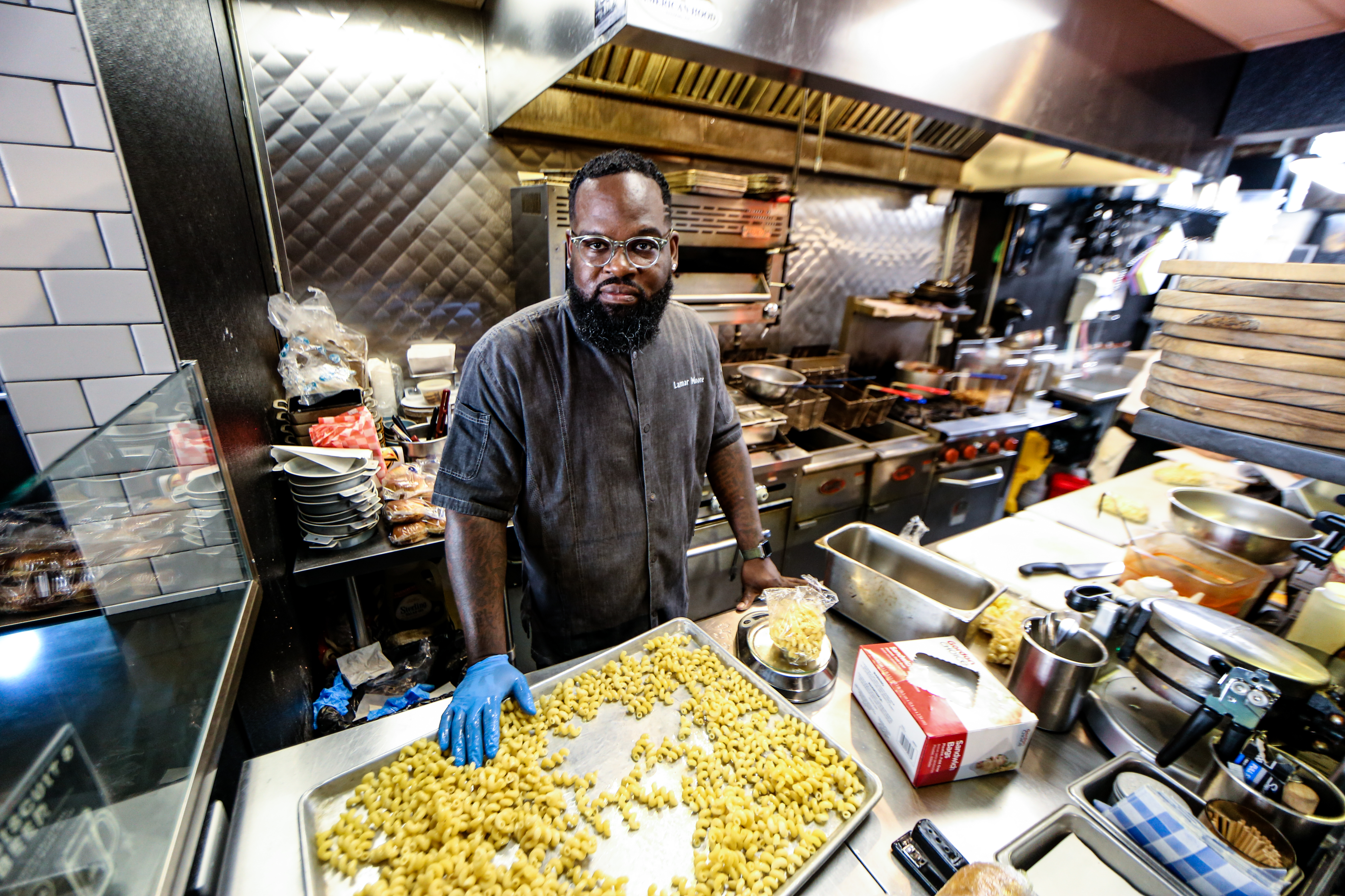 Chef Lamar Moore stands in the Swill Mill's kitchen, behind a full counter of cooking equipment and mise en place.