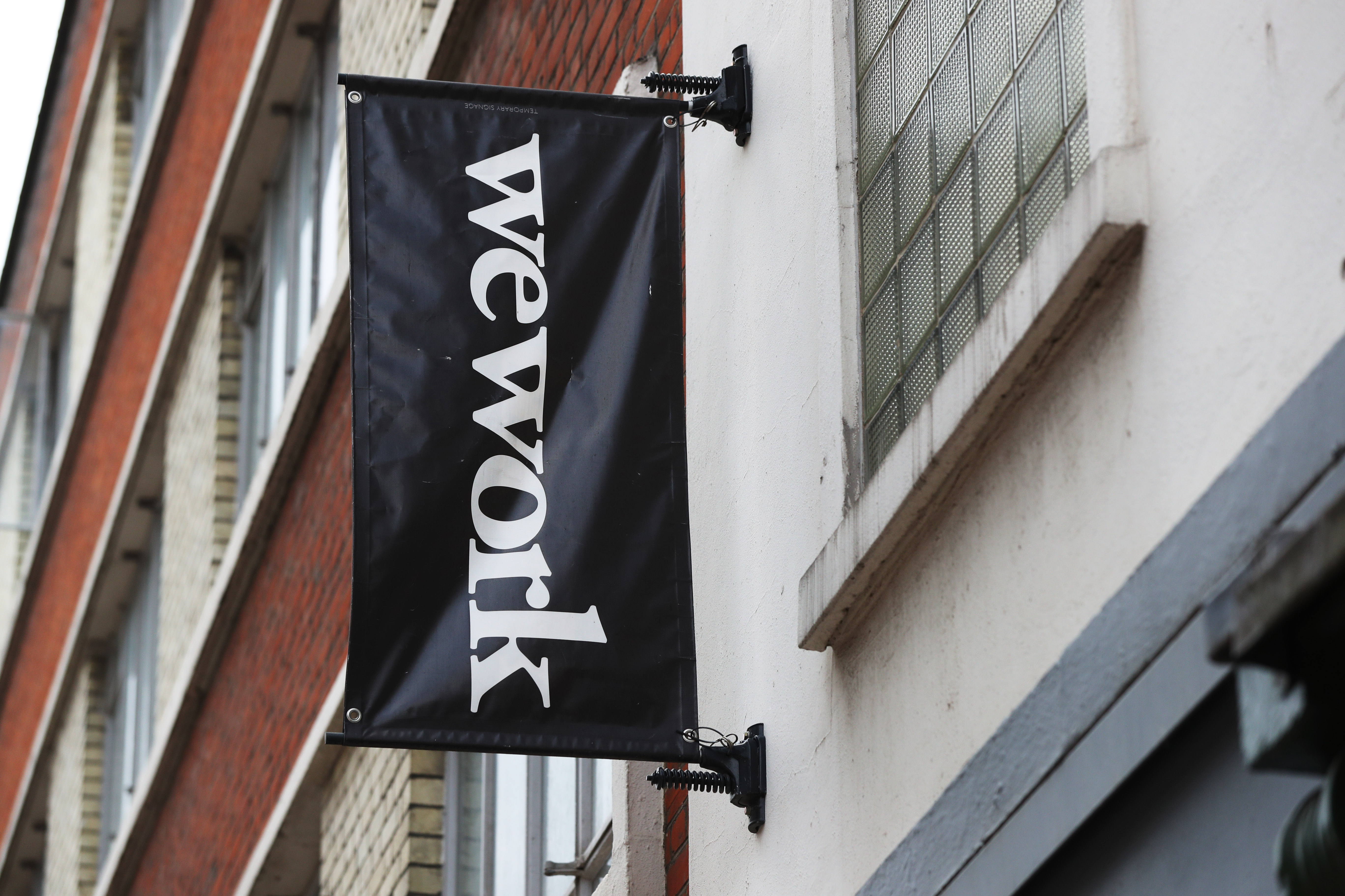 WeWork banner hanging from a building exterior.