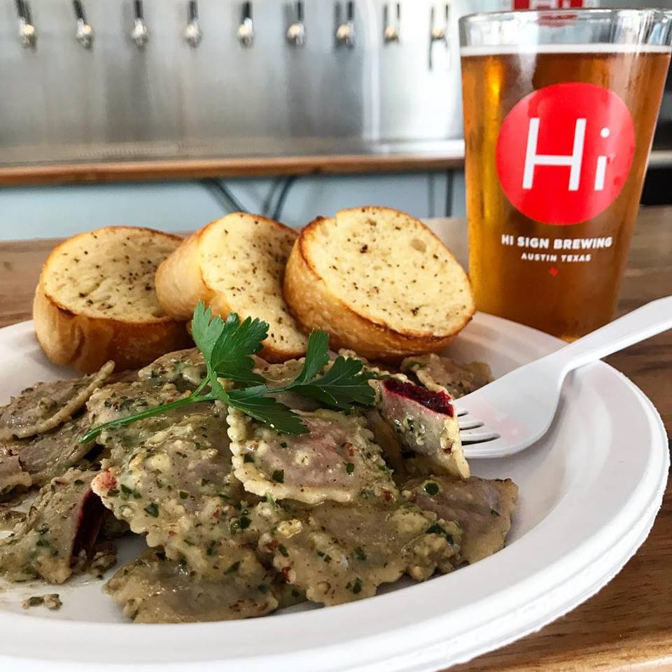 Ravioli with pecan pesto in front of a wall of tap beers and a hi sign glass of beer