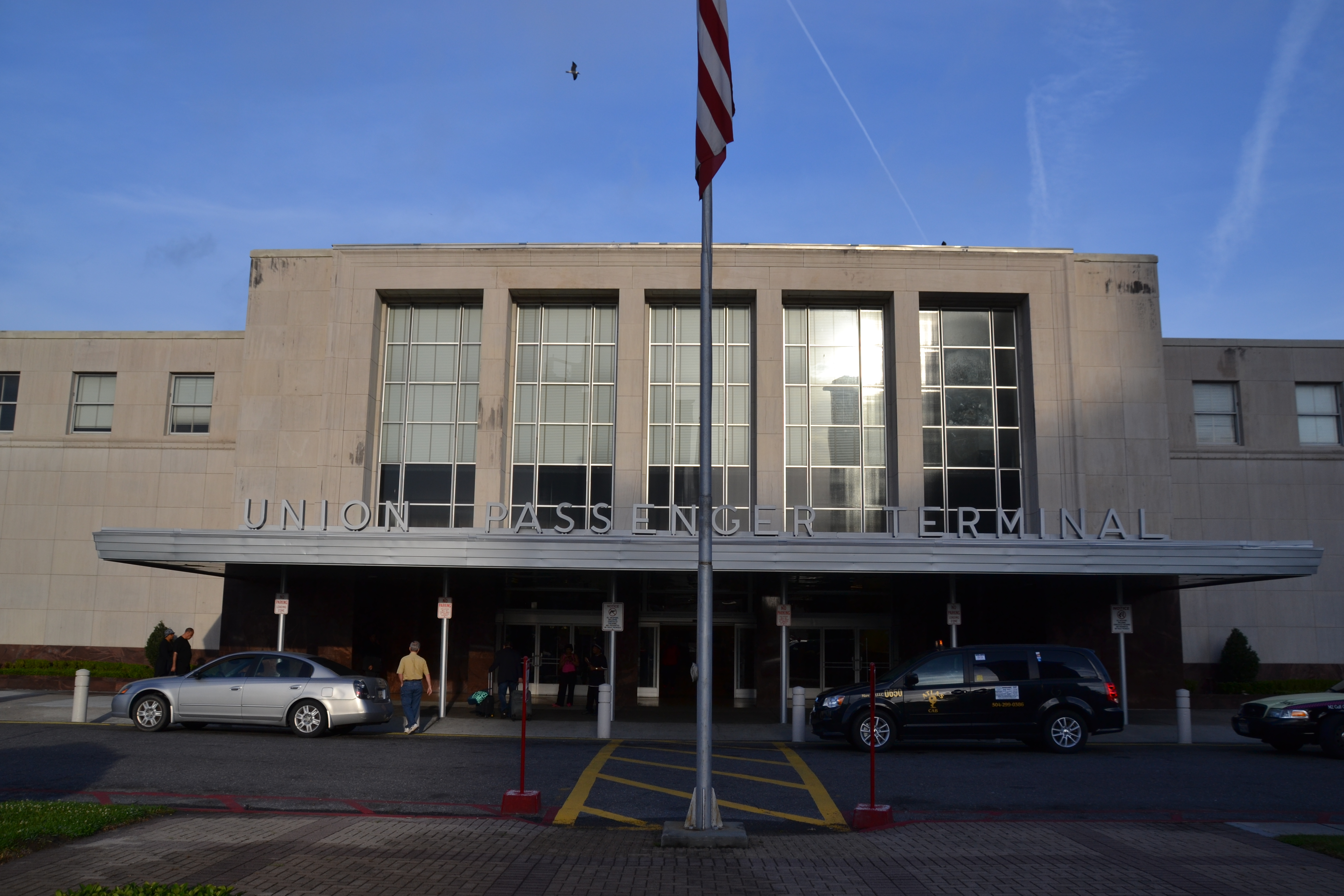 A blocky, circa-1954 train station exterior sits behind an American flag.