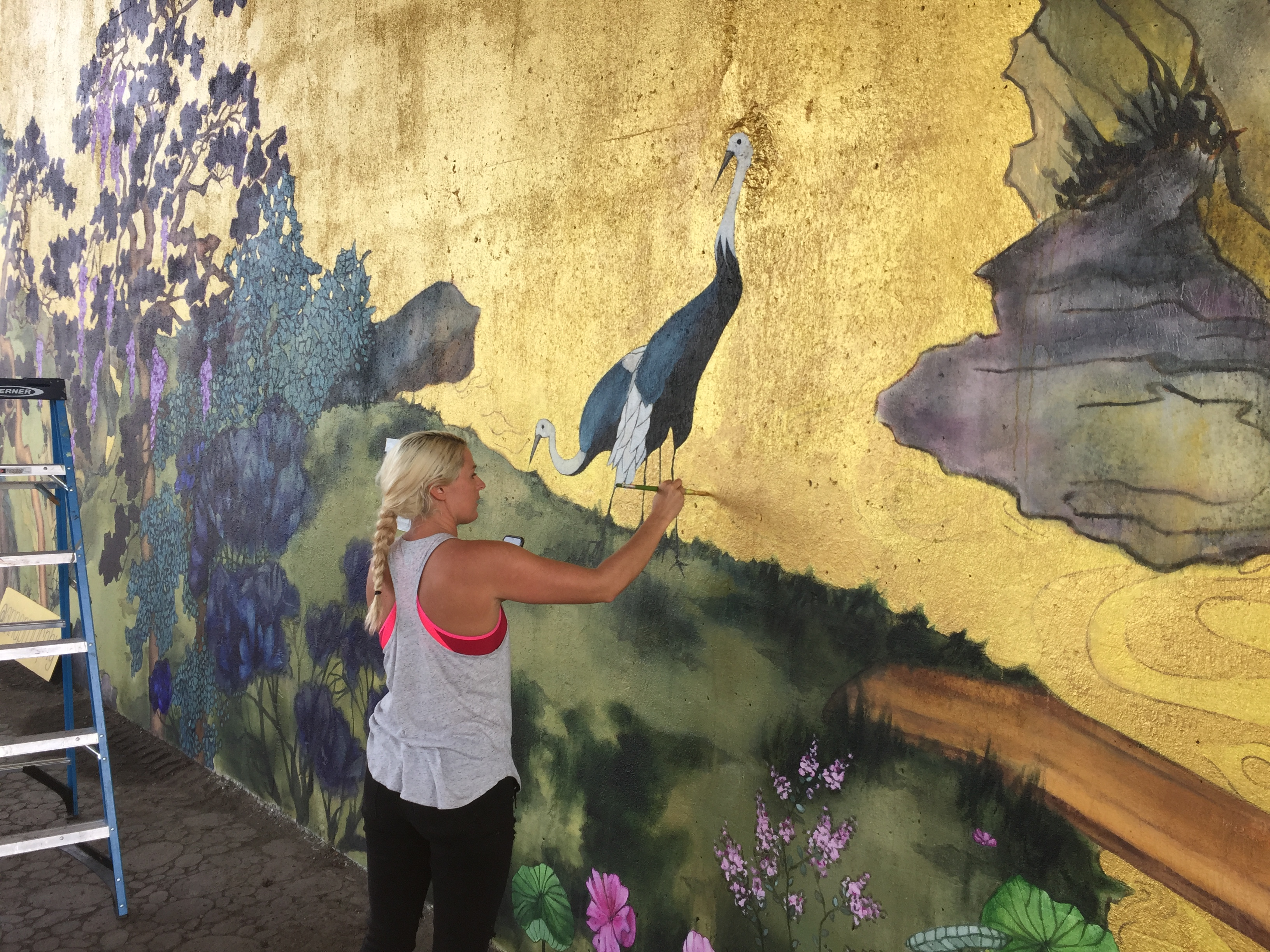 "Anna Murphy works on her new mural, ""Between the Mountains and the Water."""