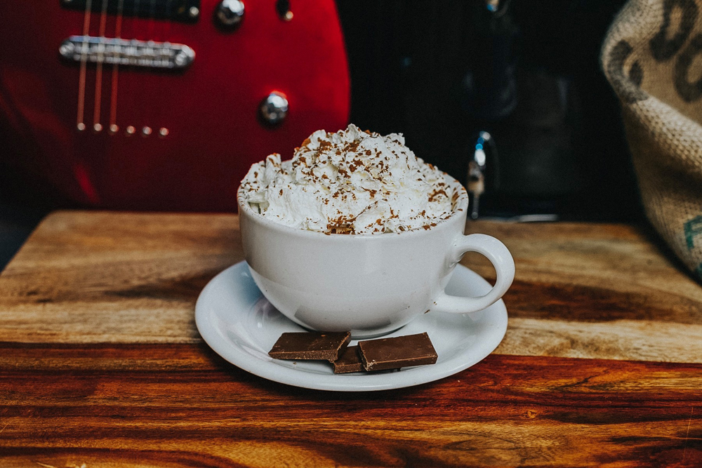 A latte coffee, piled high with whipped cream poses in front of an eclectic guitar.
