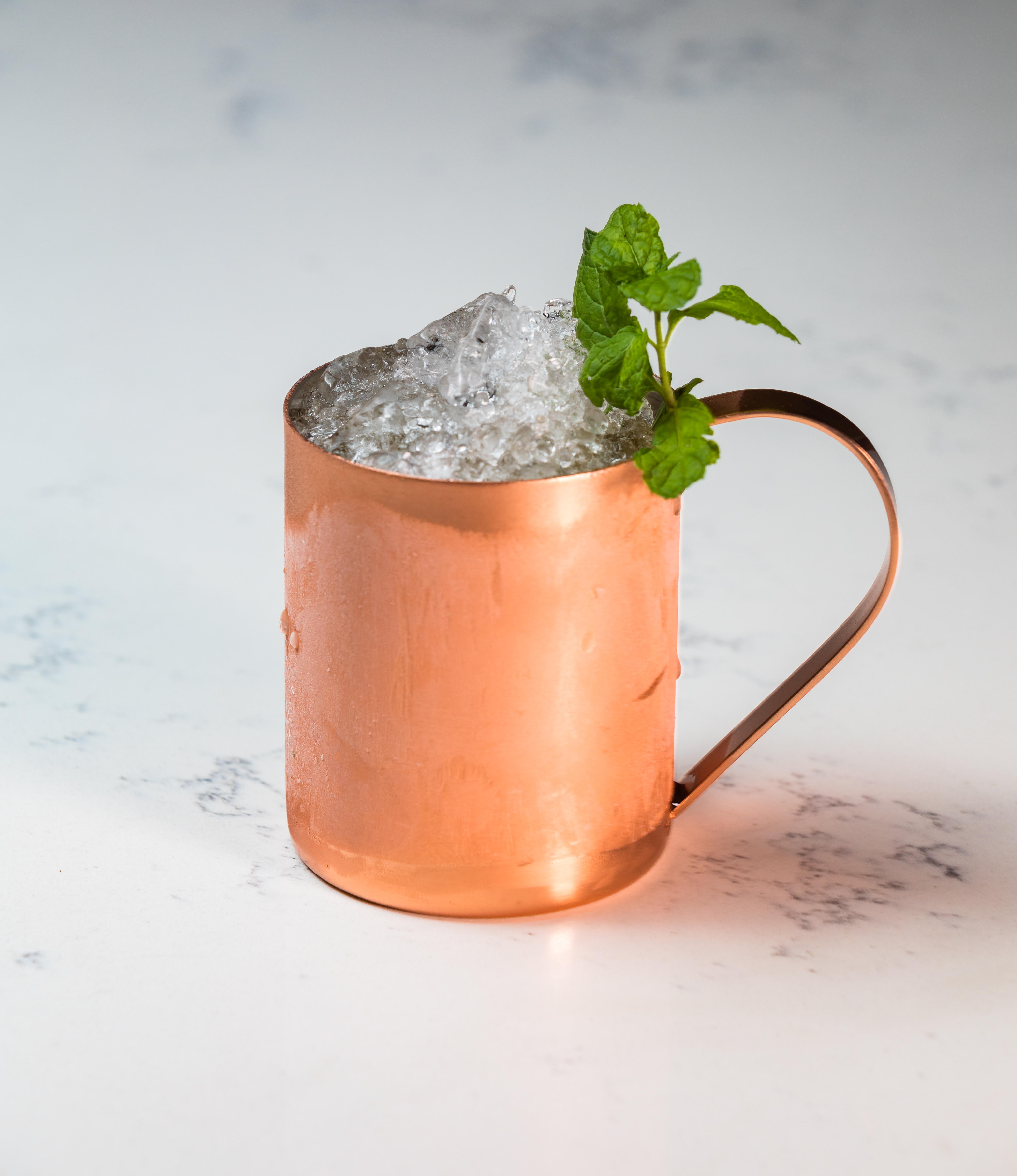 A frosted copper Moscow Mule mug contains a drink topped with ice and a sprig of green leaves.