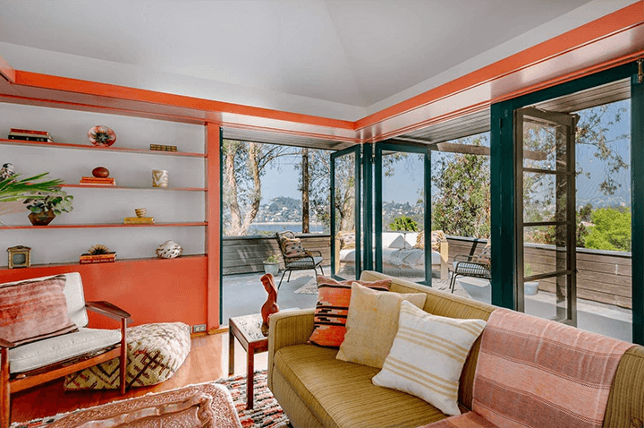 A photo of a bright room with orange walls, built-in shelves, and three sets of French doors at the corner of the room.