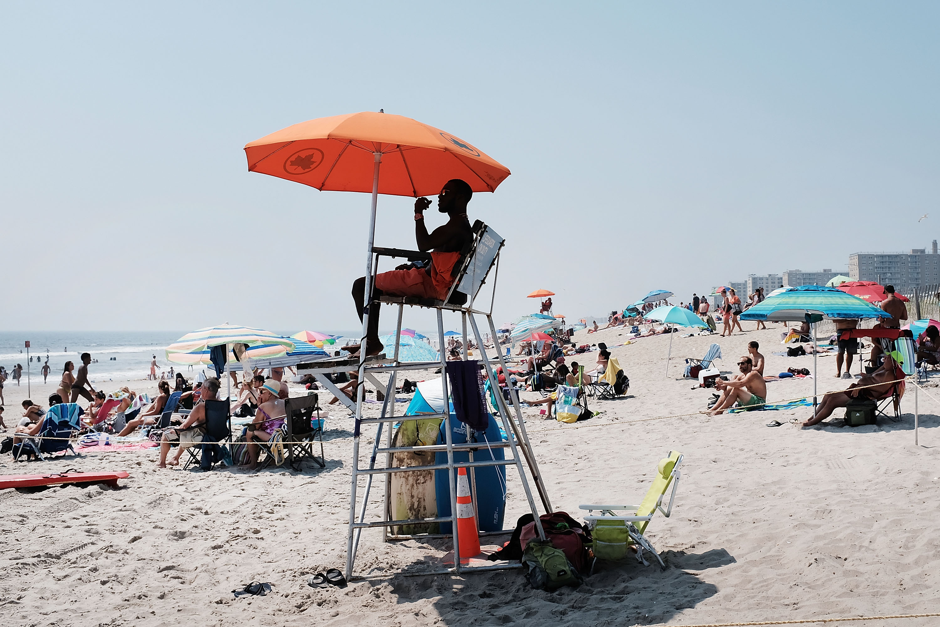 A lifeguard sits in an elevated chair with an orange umbrella on a crowded beach.