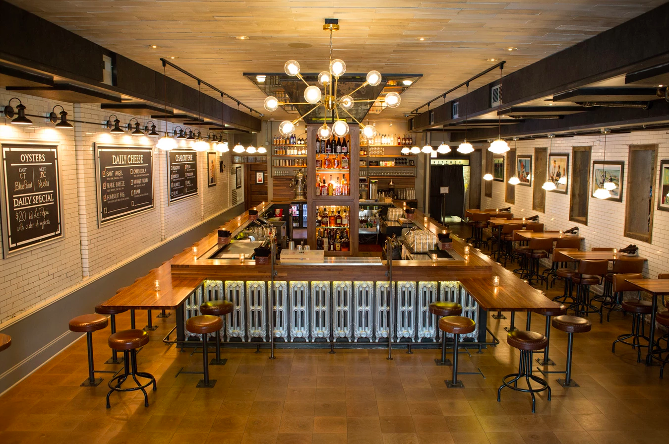 A view of high above a sunken bar room with a large rectangular central wooden bar, wooden tables, brass fixtures, twinkling lights, and chalkboards on the white brick walls.