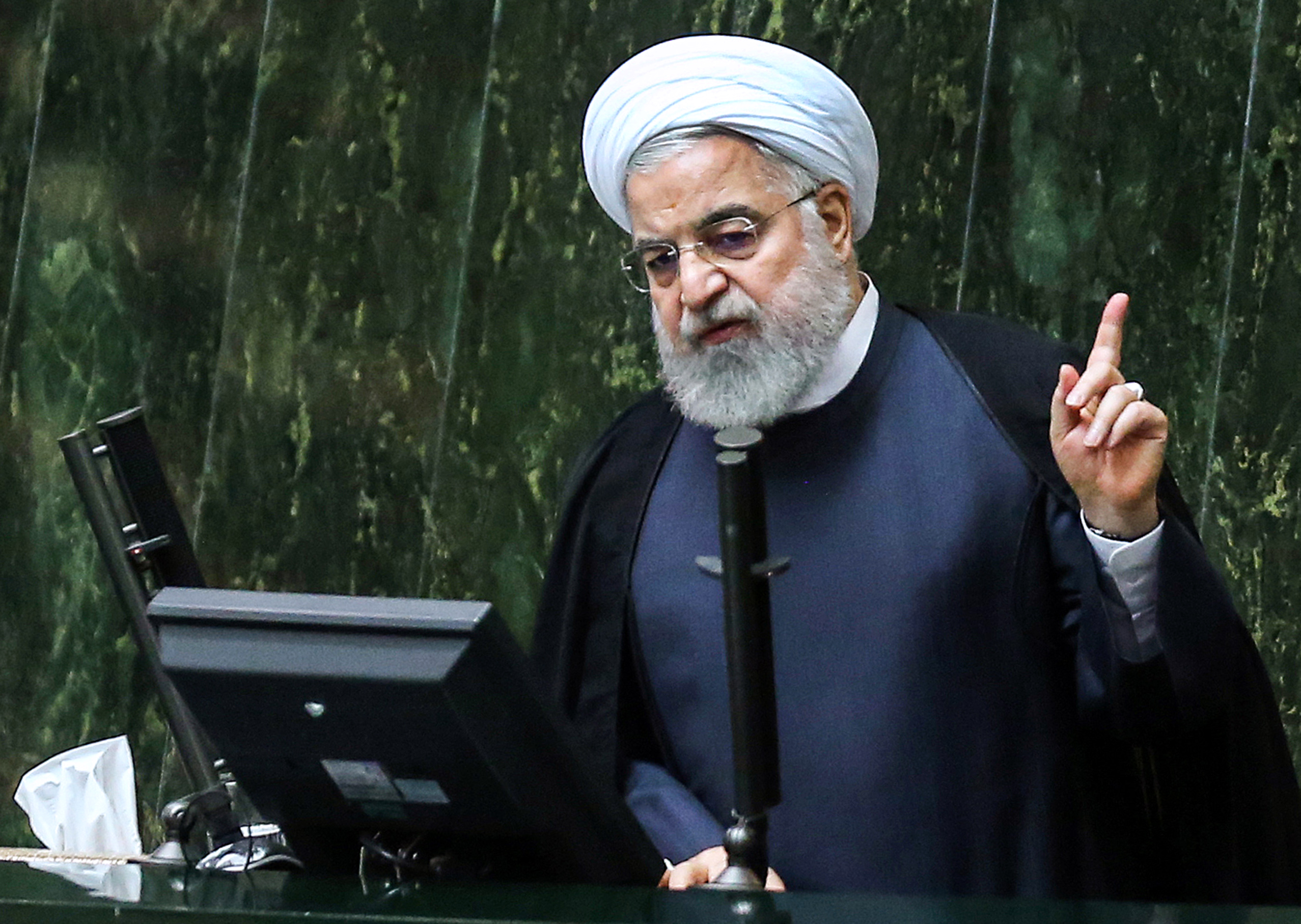 Iranian President Hassan Rouhani raises a finger while speaking at a podium.