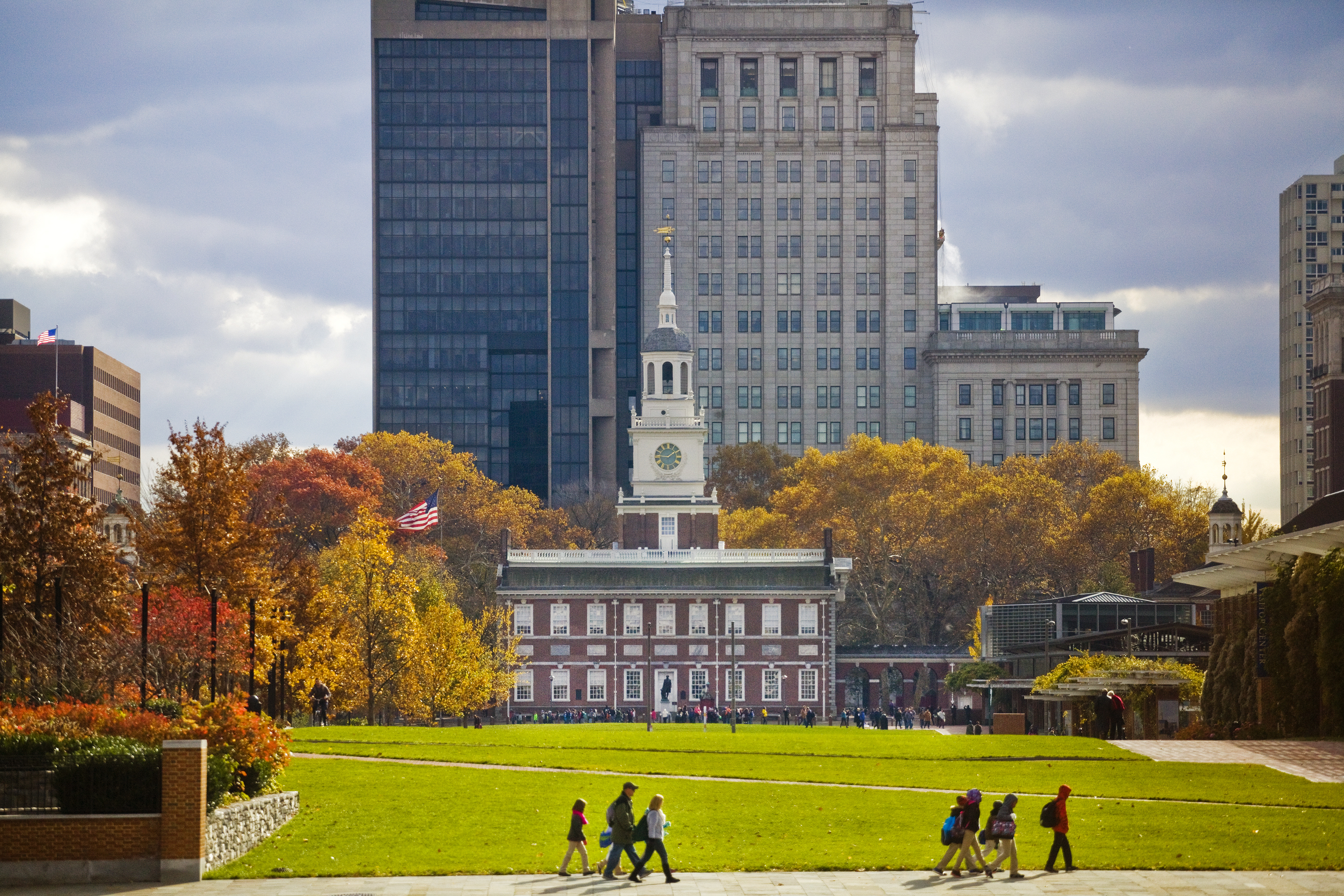 The exterior of Independence Hall in Philadelphia. There are trees surrounding the building with multicolored autumn leaves.