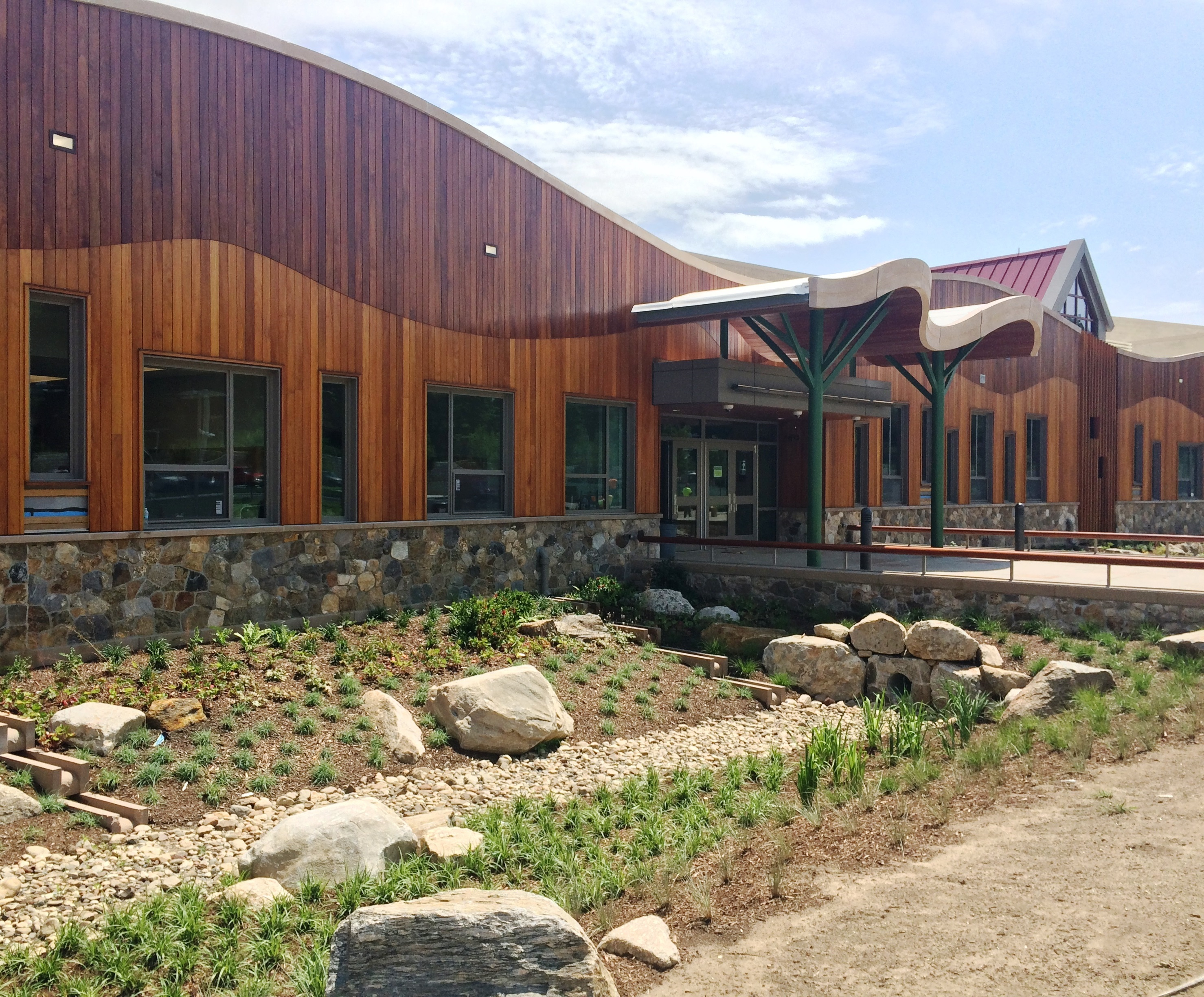 The front entrance of a wood-clad modern school, with an entryway that spans a landscaped rock garden.