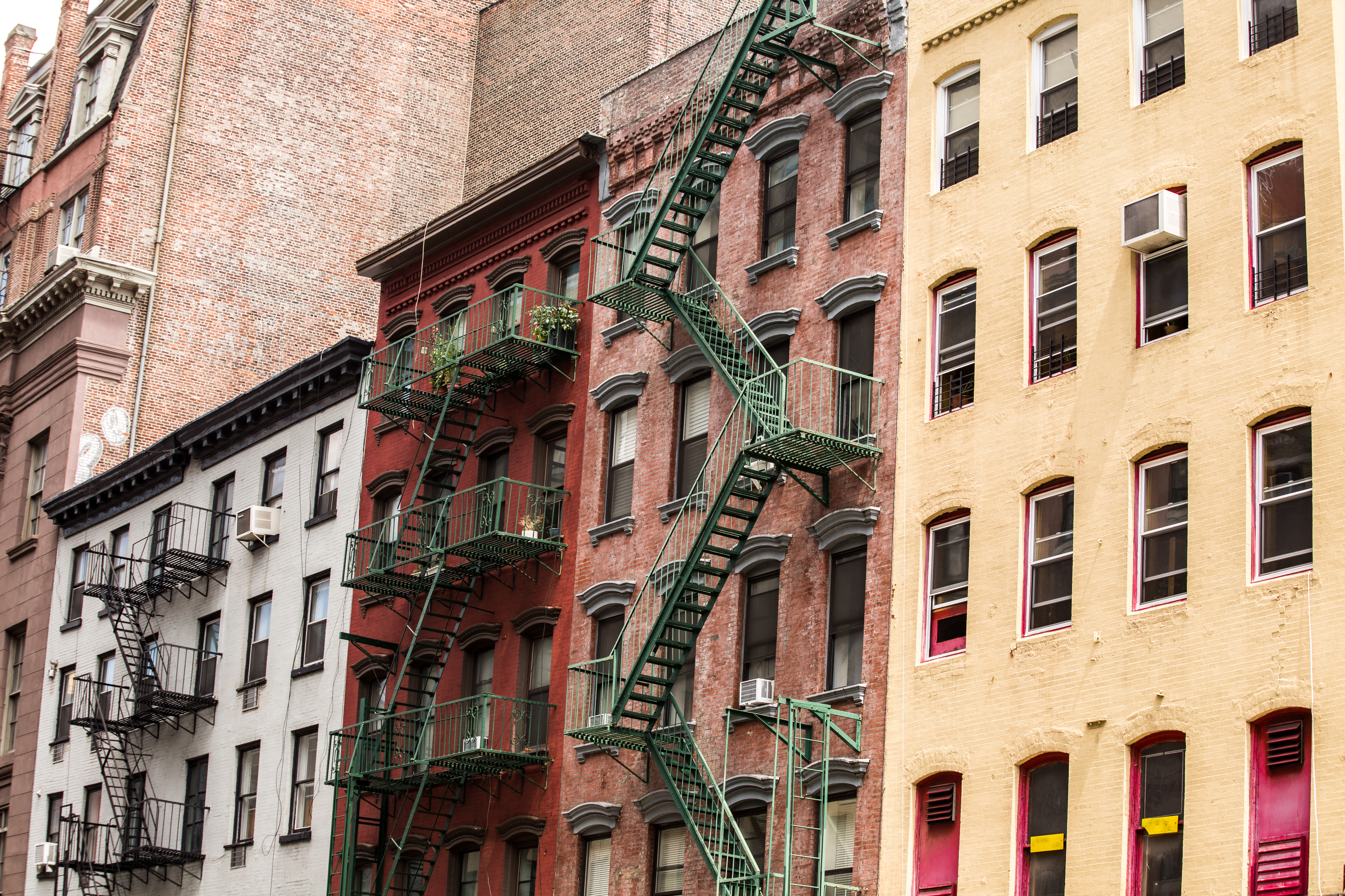 Four colorful NYC tenement buildings next to each other, three of them with fire escapes.