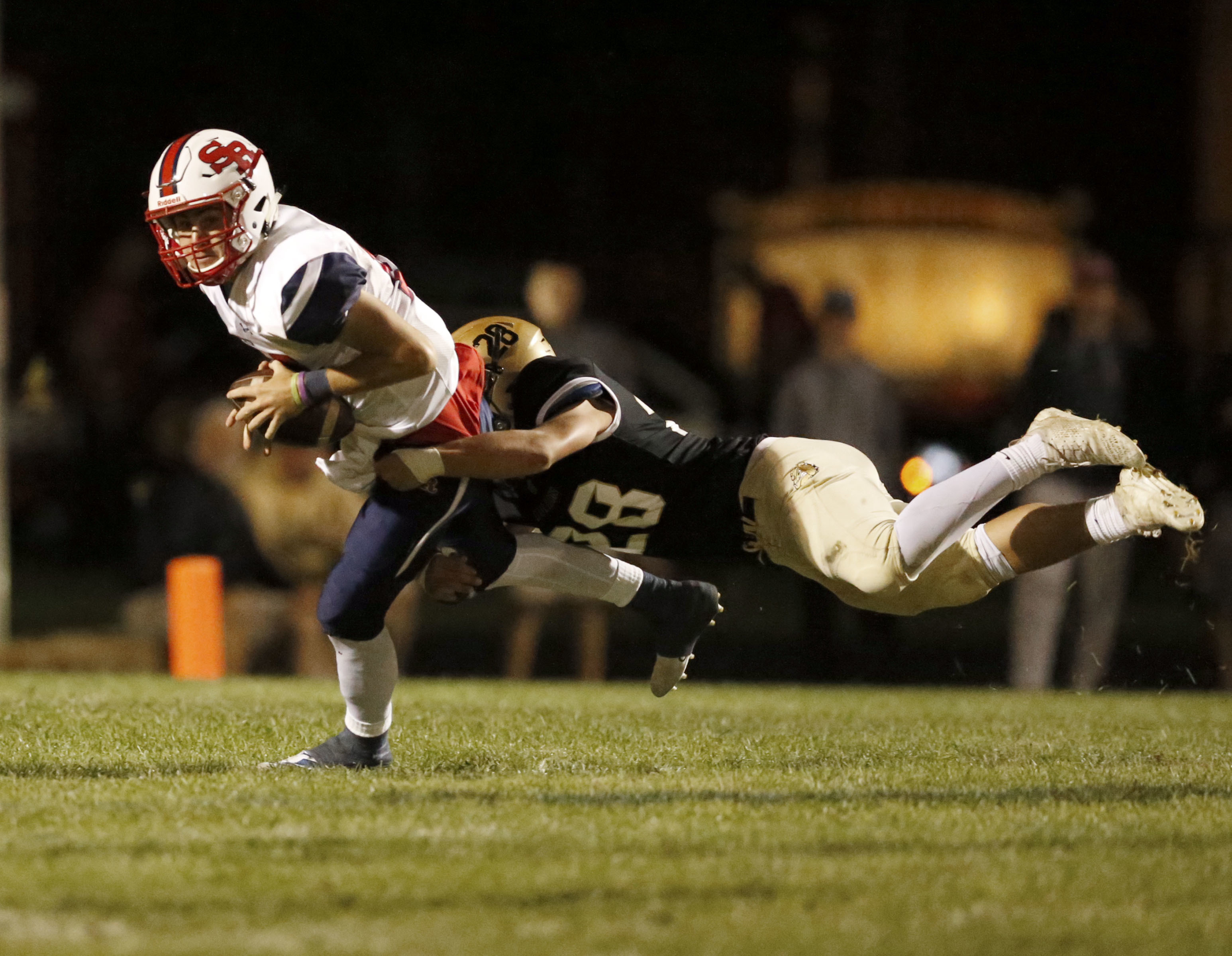 St. Rita's Brian Johnson (14) is tackled for a loss by Richards' Nick Houston (28).