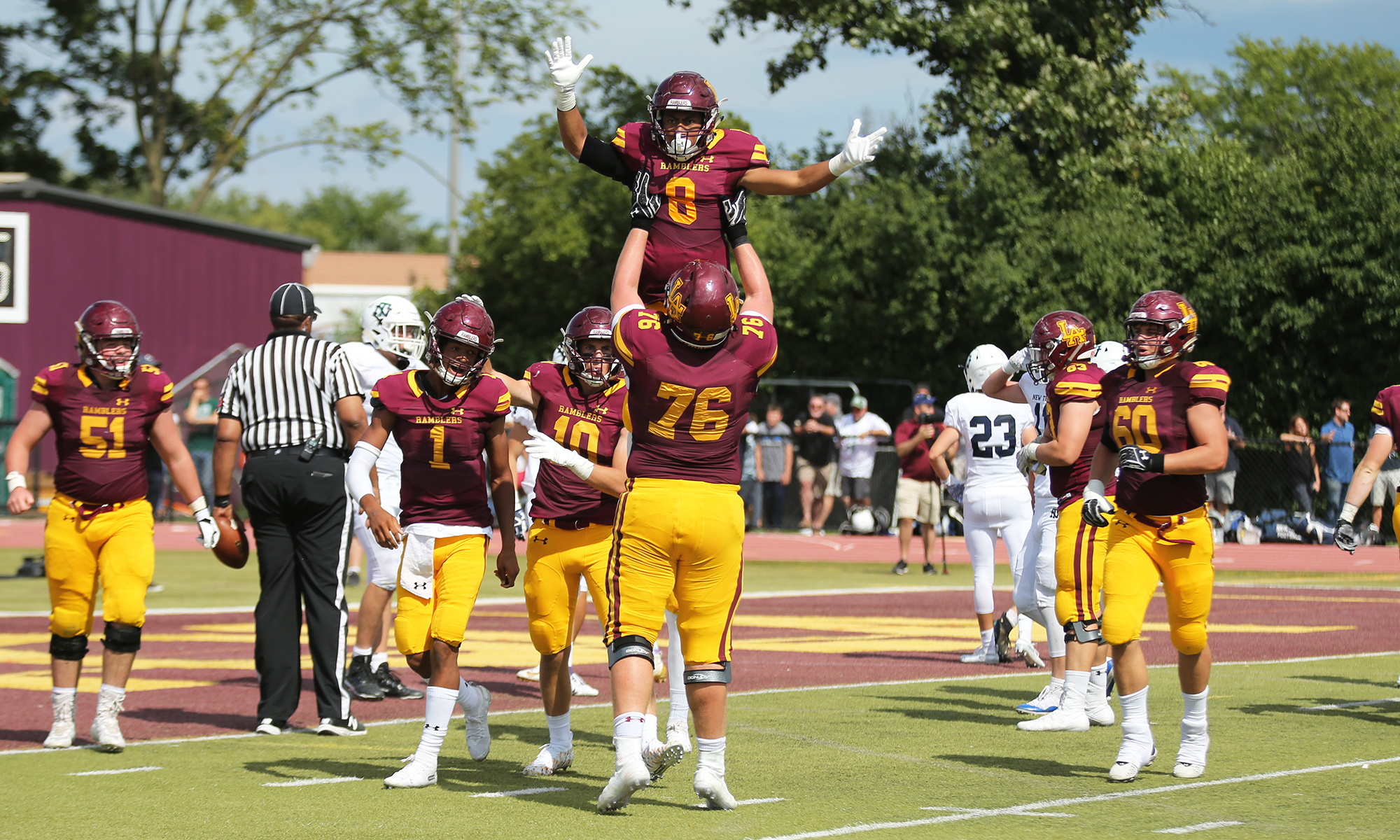Loyola's Trevor Cabanban (8) scores a touchdown and gets a lift from Christo Kelly (76).