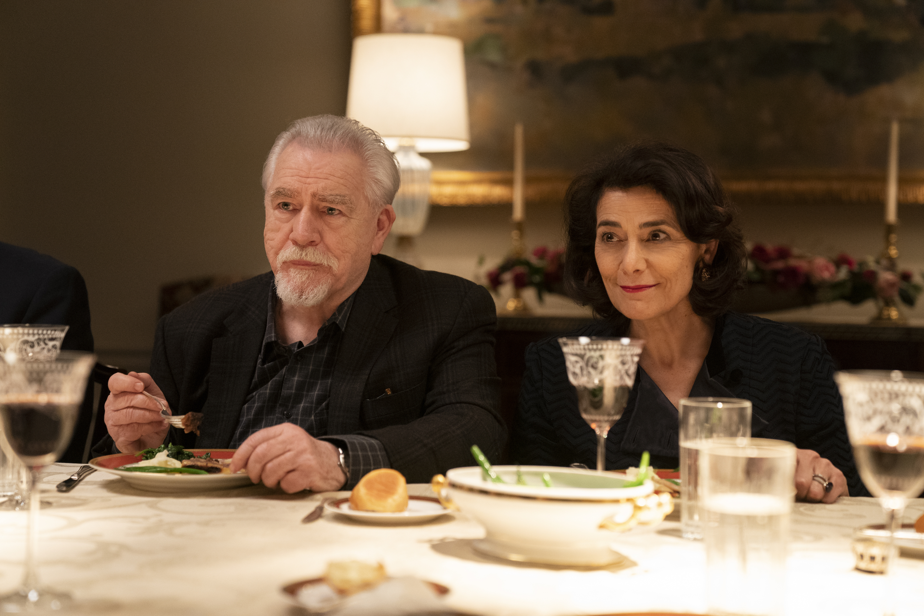 Logan (Cox) and Marcia (Abbass) sit at a dining table.