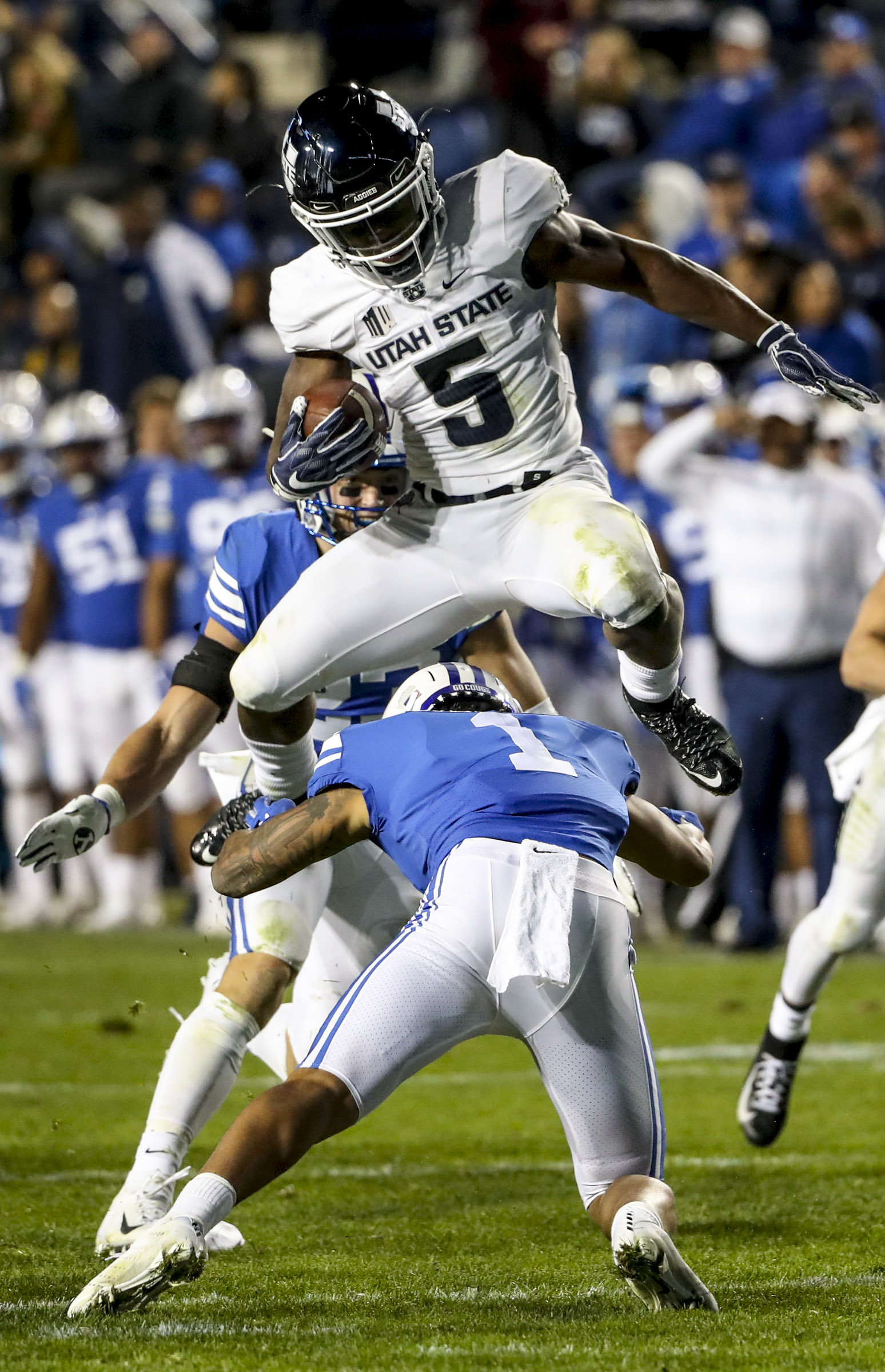 Utah State Aggies wide receiver Ron'quavion Tarver (1) hurdles Brigham Young Cougars defensive back Troy Warner (1) as he runs up the middle during the Utah State versus BYU football game at LaVell Edwards Stadium in Provo on Friday, Oct. 5, 2018.