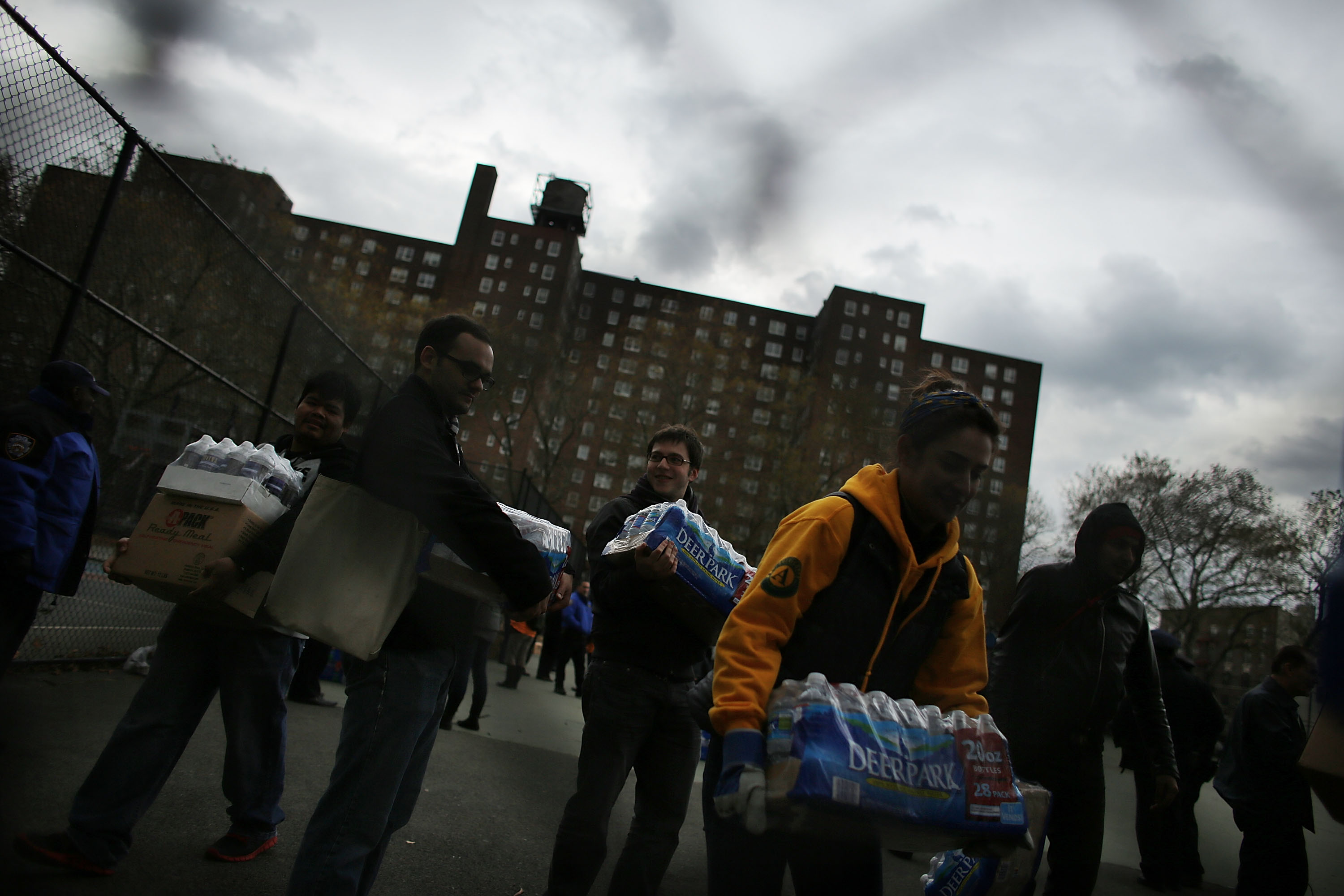 Through a chainlink fence a half dozen volunteers hold packages of bottled water. In the distance, a brown high-rise building part of the Red Hook Houses public housing complex can be seen.