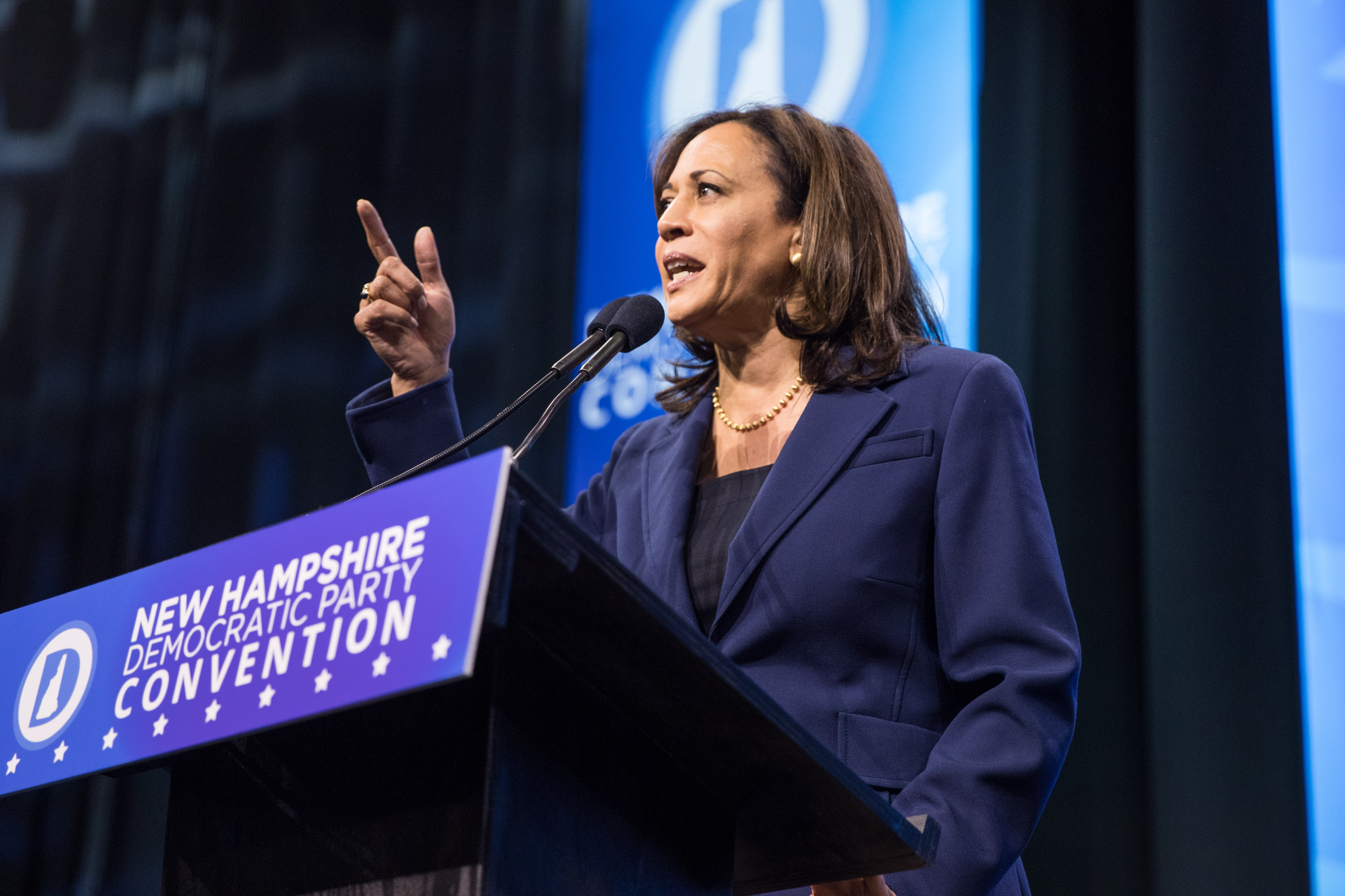Kamala Harris speaking and pointing from behind a podium at the New Hampshire Democratic Party Convention.