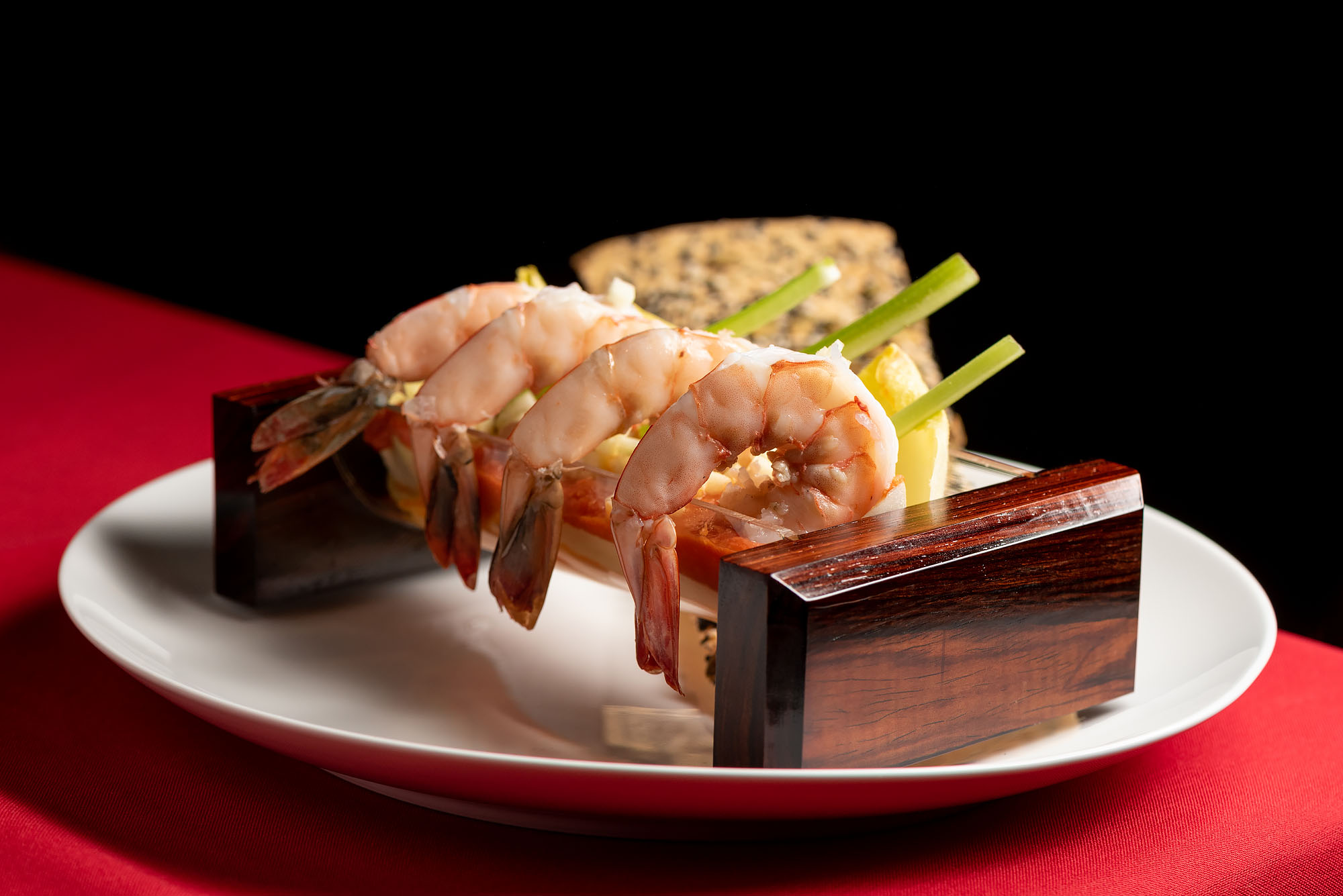 A skewer of shrimp assembled horizontally on a plate with a red tablecloth beneath.