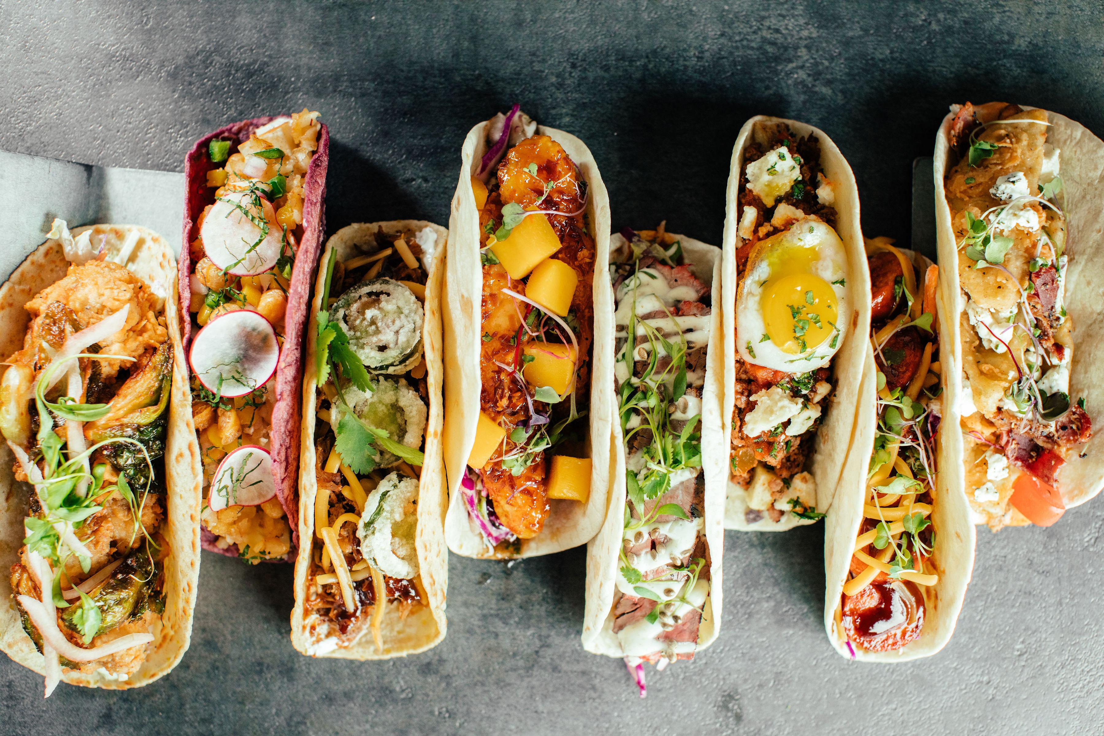 A row of various eight flour tortilla tacos