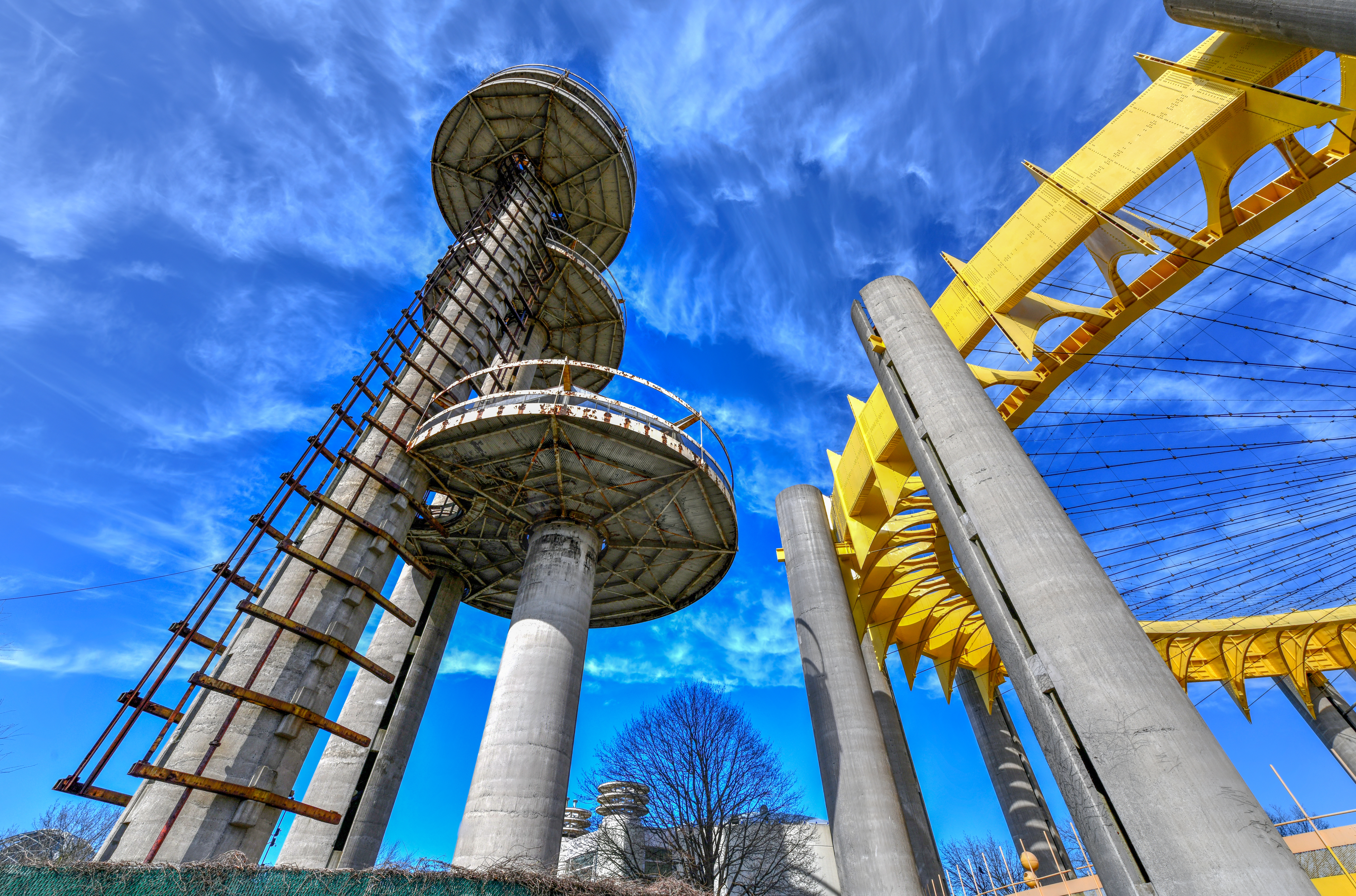 Three tall towers and a smaller round one painted in yellow rise above Flushing Meadows-Corona Park.