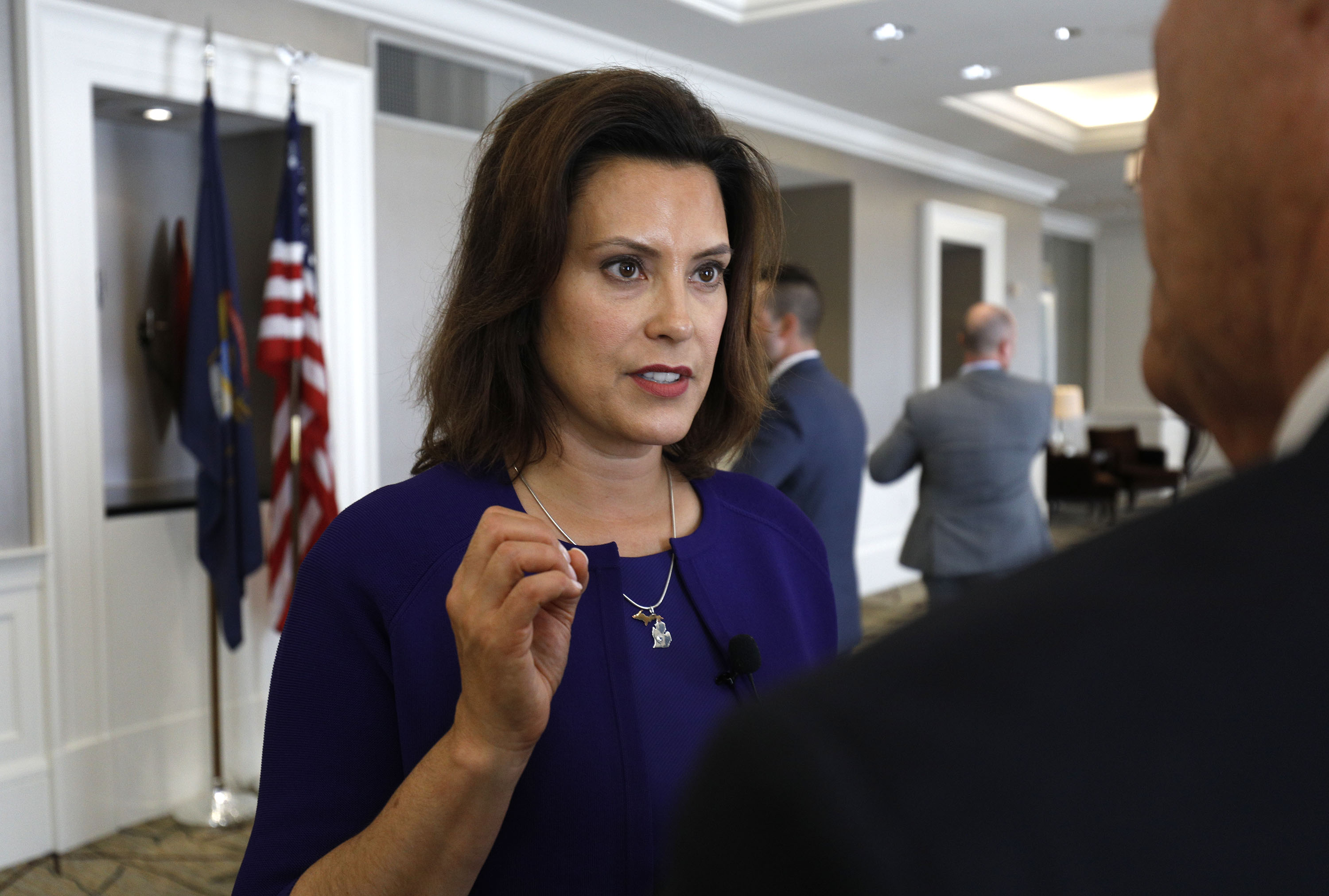 Michigan Governor Gretchen Whitmer speaks to a reporter. She's a white woman with dark brown hair down to her shoulders. She's wearing a blue dress suit and a diamond necklace.