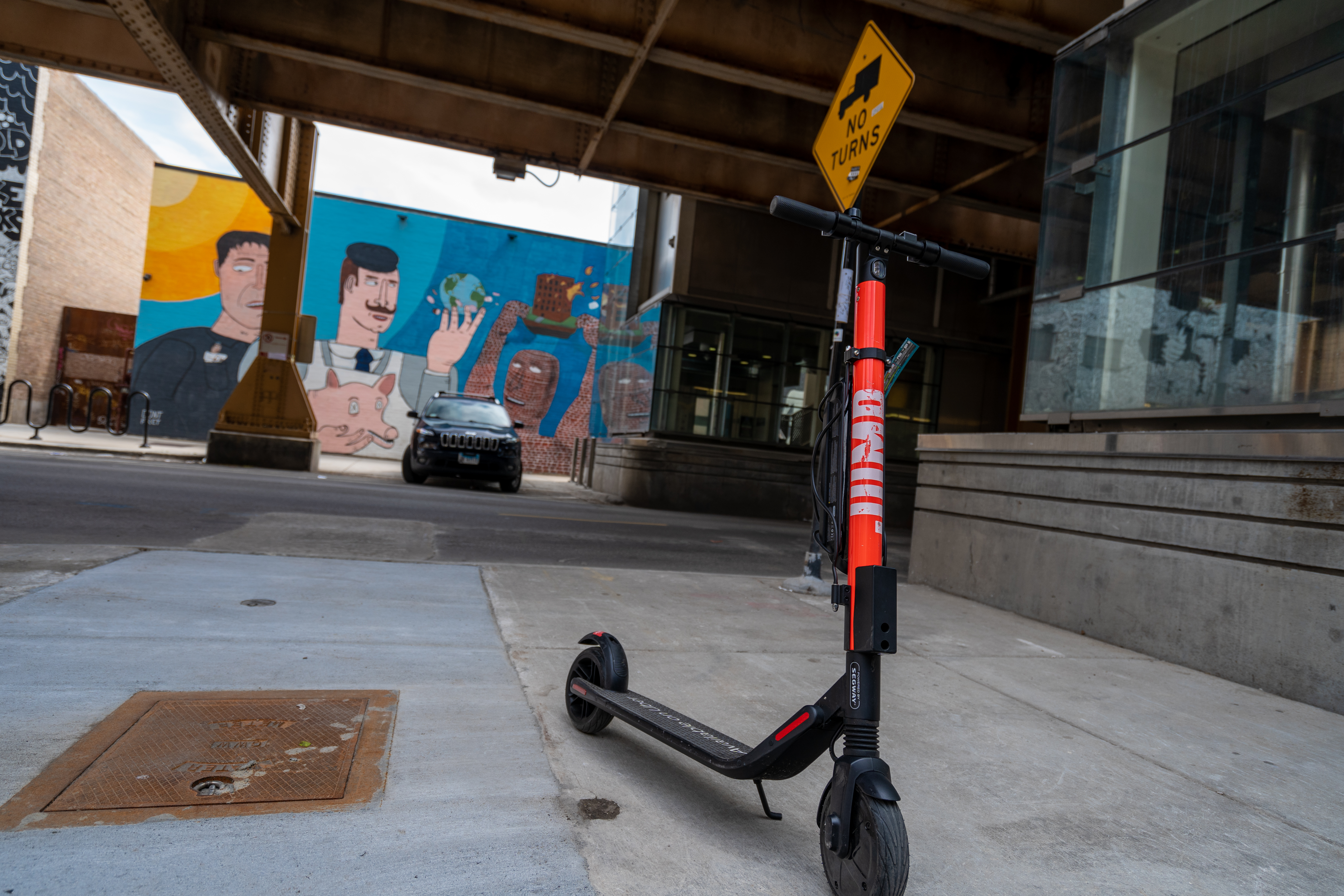 A Jump e-scooter parked on the sidewalk corner near L tracks with a colorful mural in the background