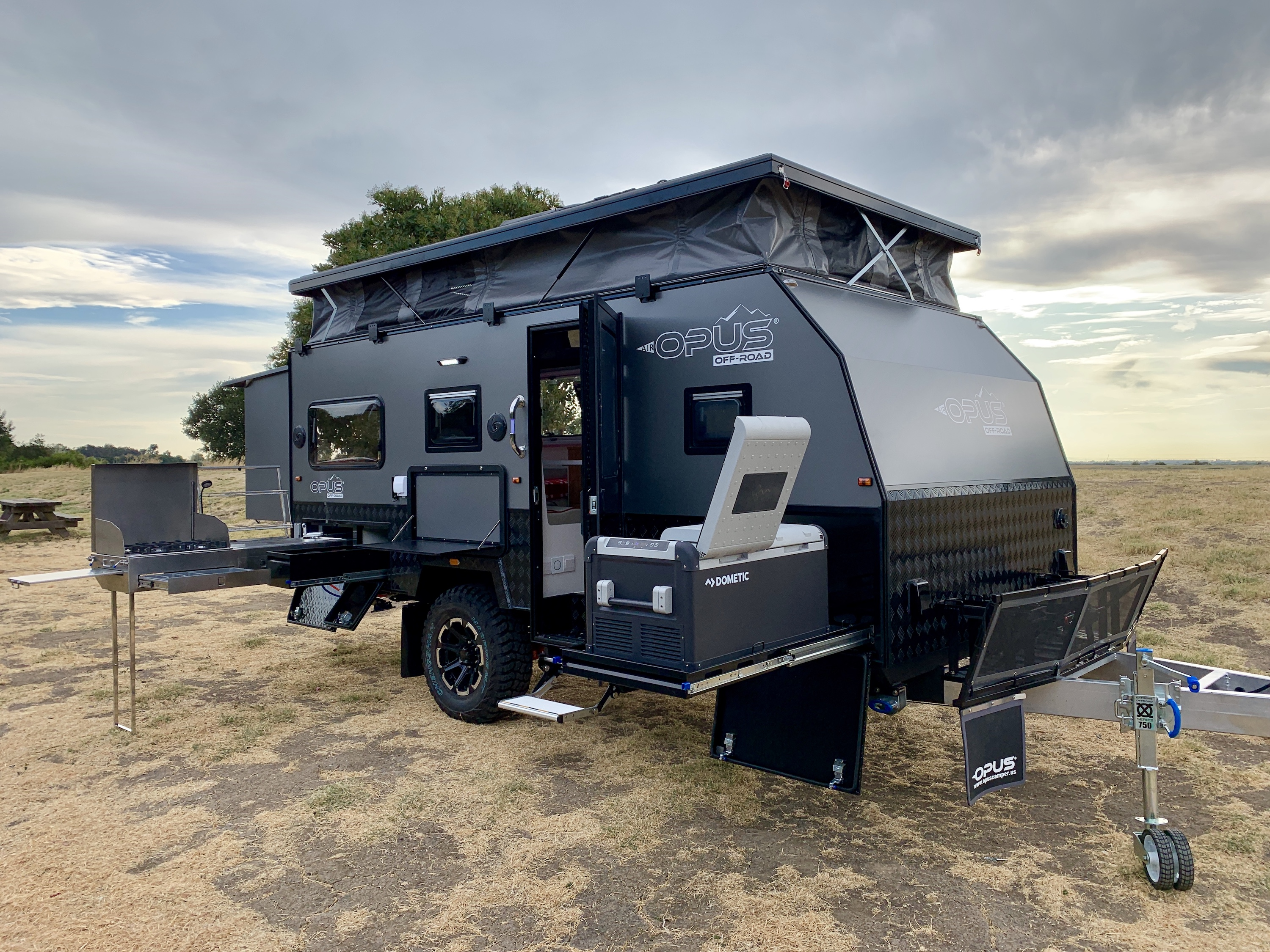 A black and gray overland travel trailer features a pull-out fridge, a slide-out outdoors kitchen with stove and sink, and a pop-up roof. The camper sits in an open field with a cloudy sky.