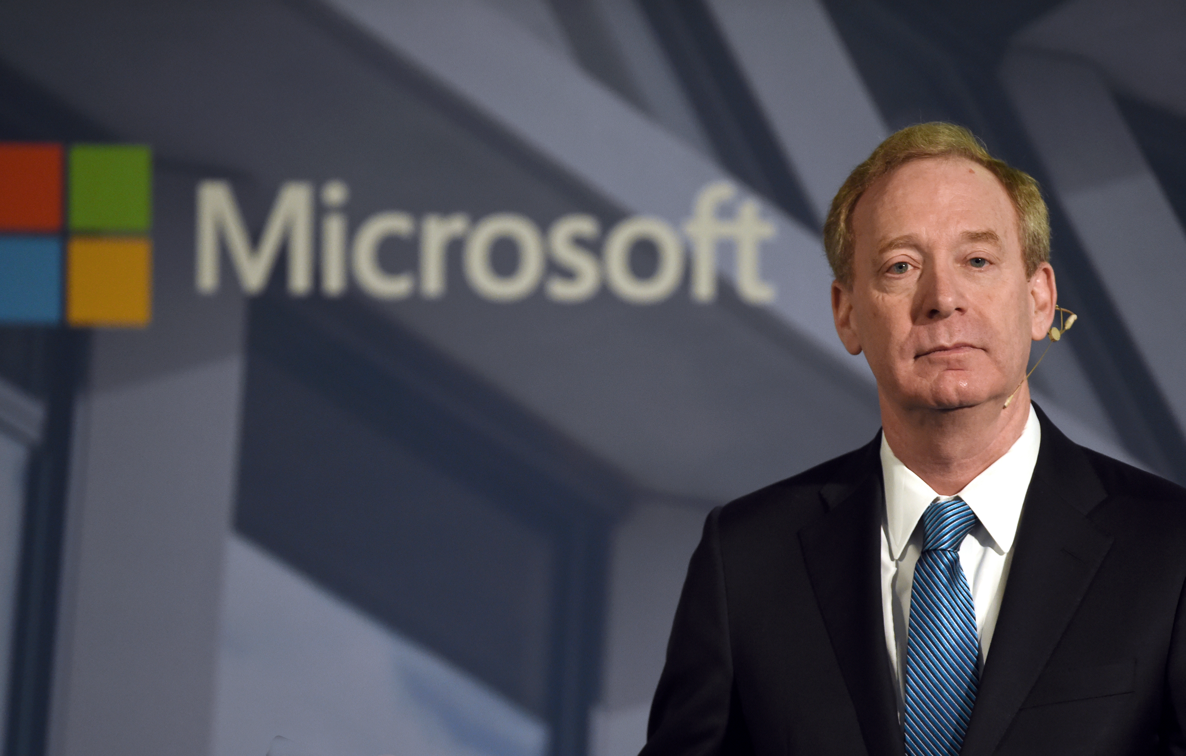 "Microsoft President Brad Smith, the co-author of the new book ""Tools and Weapons: The Promise and the Peril of the Digital Age,"" standing beside a Microsoft logo and the word ""Microsoft."""