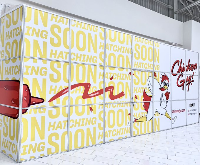 A papered over mall stand with a running chicken in sunglasses logo and the words Chicken Guy repeated all over it in yellow font