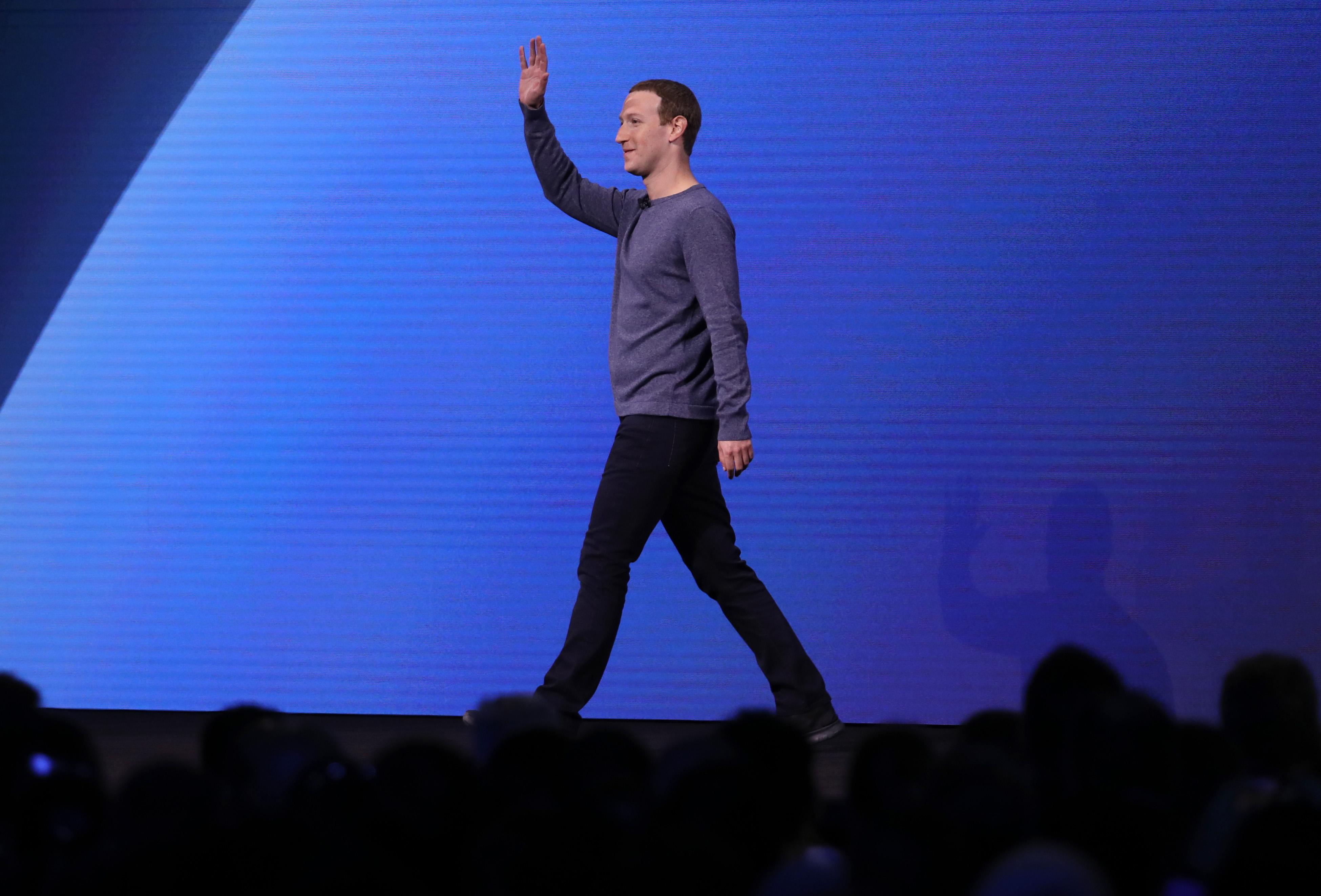 Facebook CEO Mark Zuckerberg walking onstage and waving.