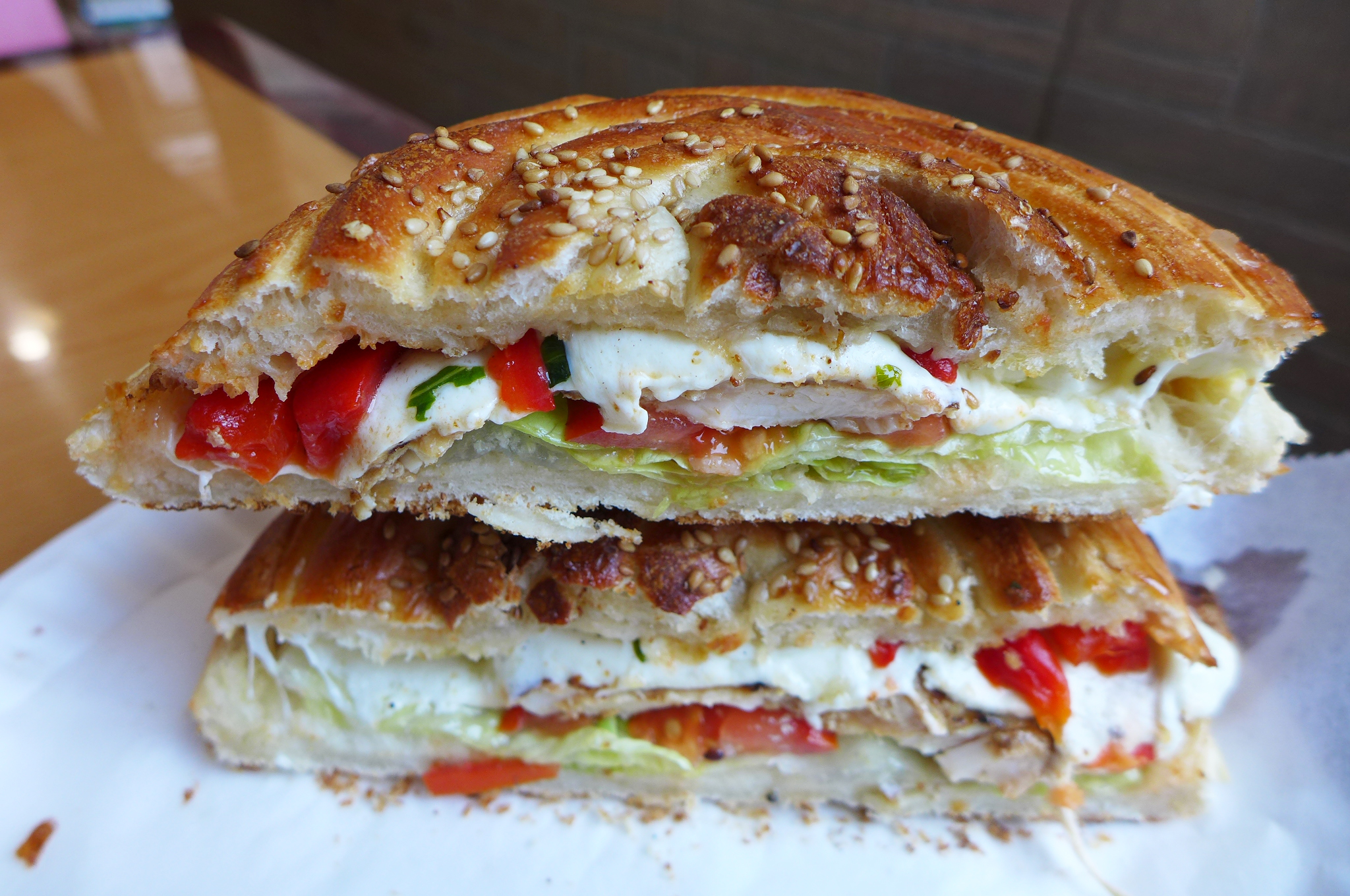 Round sandwich with grilled chicken and mozzarella on a sesame seeded roll...