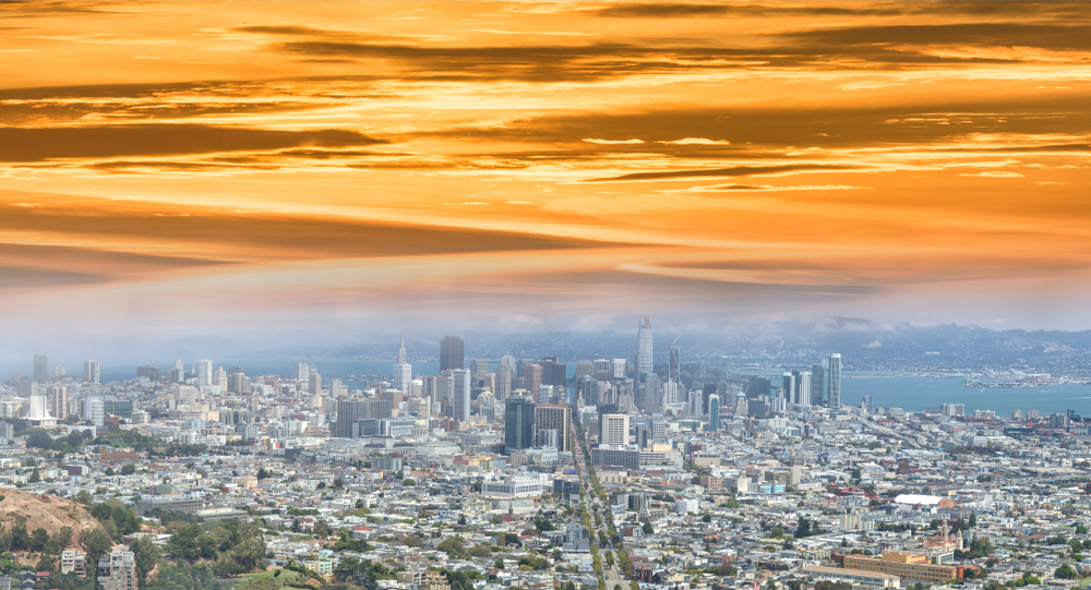 A panoramic, aerial view of buildings in San Francisco, with a layer of gray fog hovering over it and a bright orange sunset coloring the sky above that.