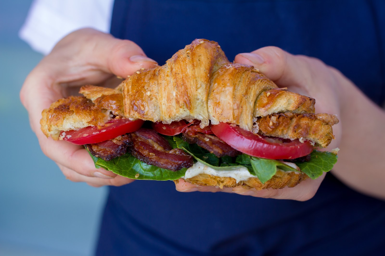 A view of hands holding a BLT on a croissant, with lamb bacon.