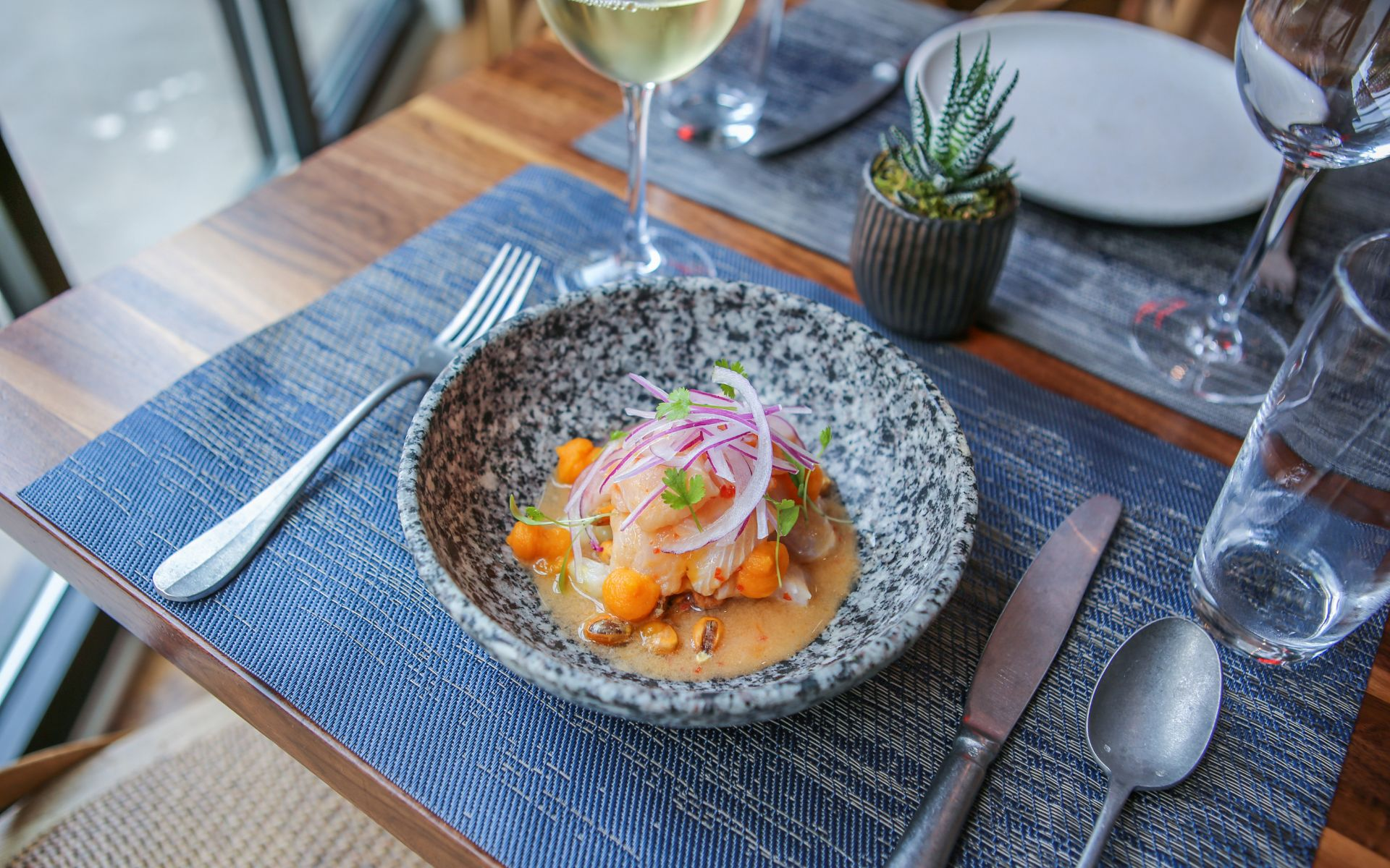 A bowl of ceviche resting on an orange sauce and topped with red onions