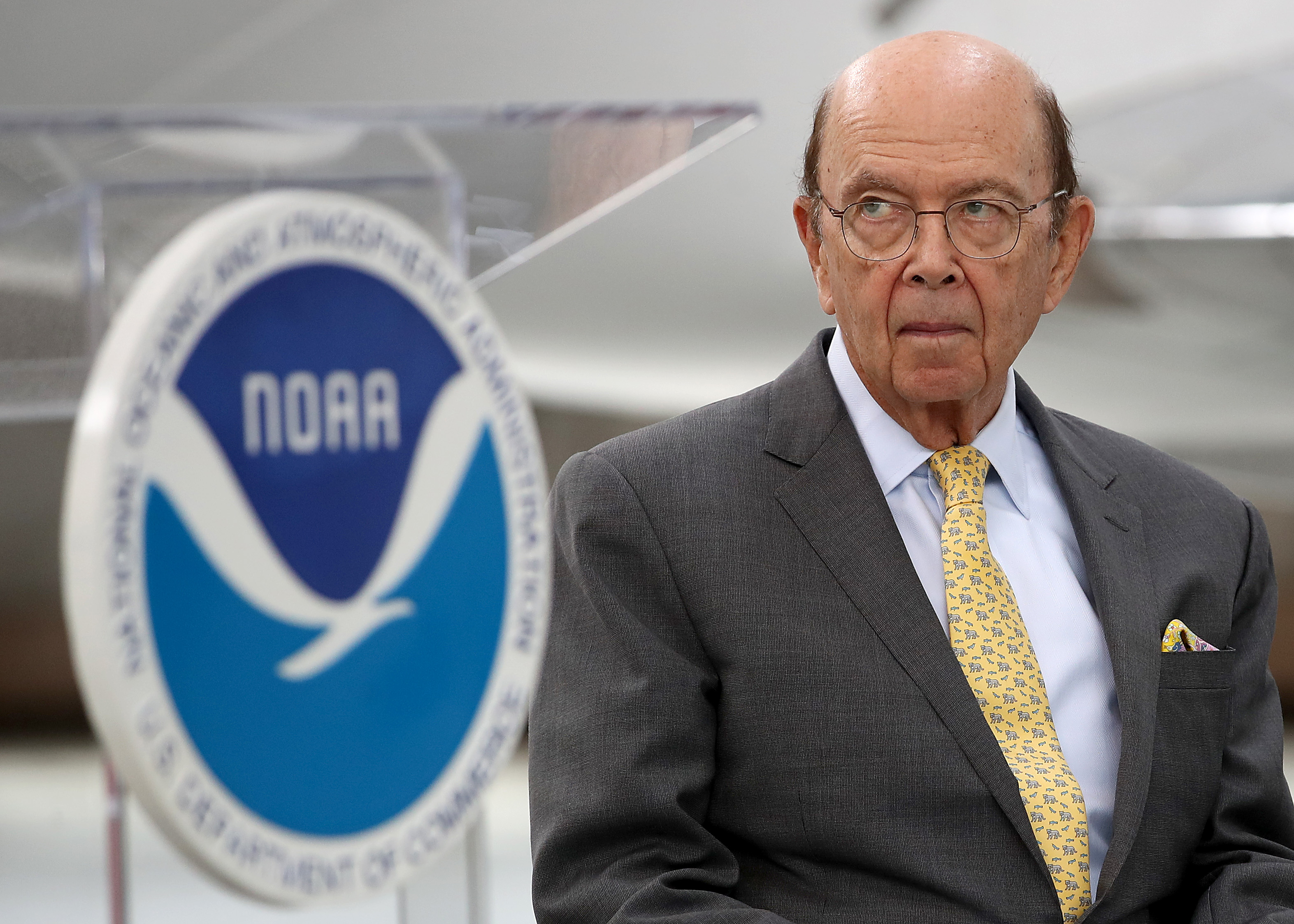 Ross, in a grey suit and yellow tie, frowns in front of the National Oceanic and Atmospheric Administration's logo.