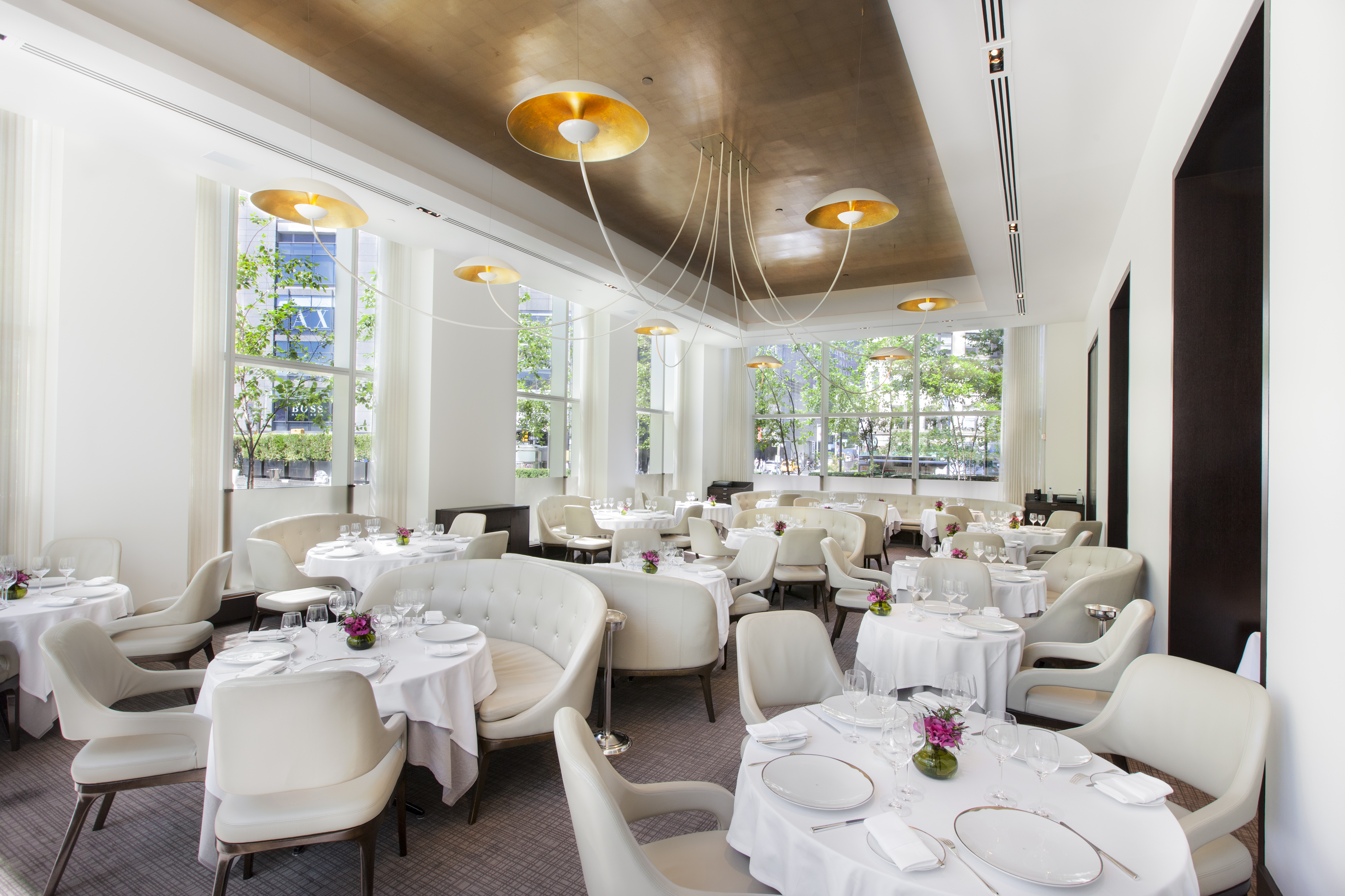 The Jean-Georges dining room, with plush cream chairs set at tables with white tablecloths