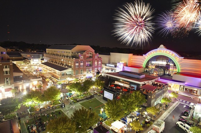Fireworks explode over a theater and shopping district with a little lawn and trees.