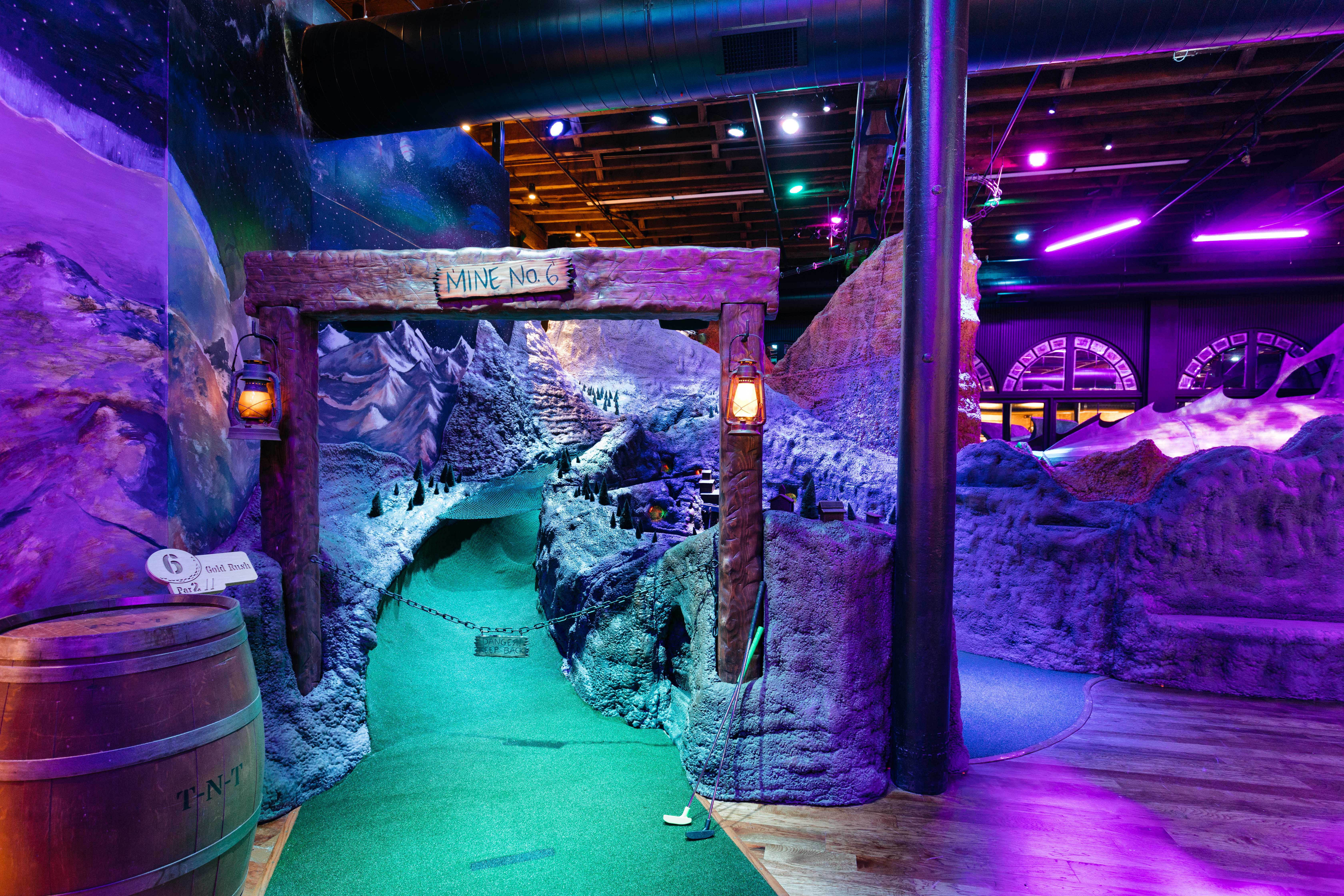 "A photo of the gold rush-themed hole at Urban Putt in Denver. The putting green goes under an old looking arch adorned with a sign stating ""Mine #6"" and into a course decorated to look like mountains."