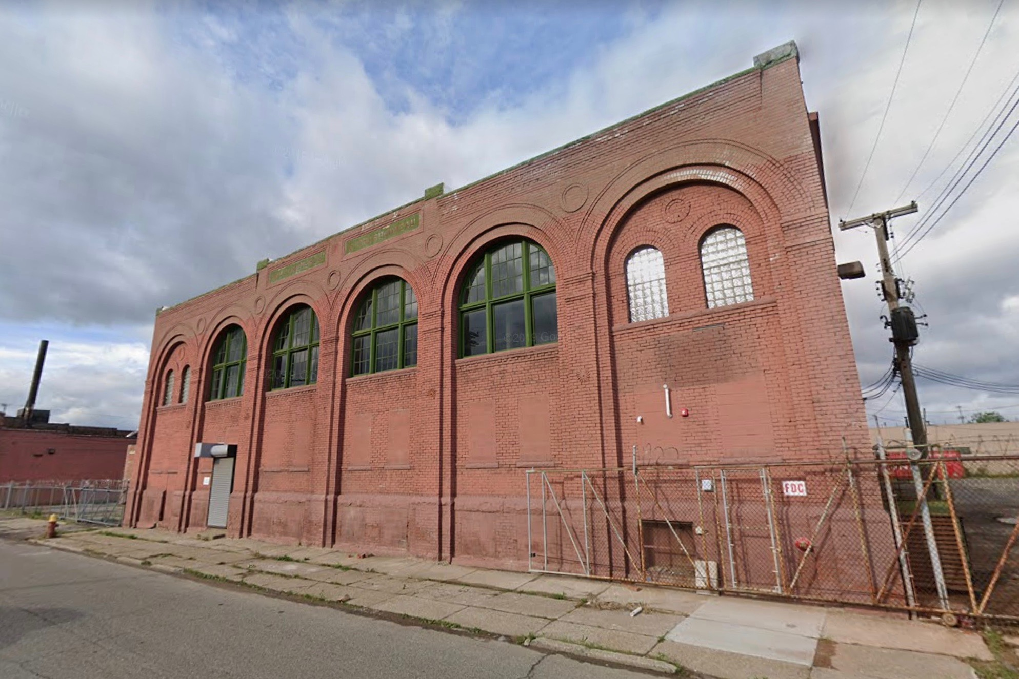 A red brick building with arched windows on the second floor.