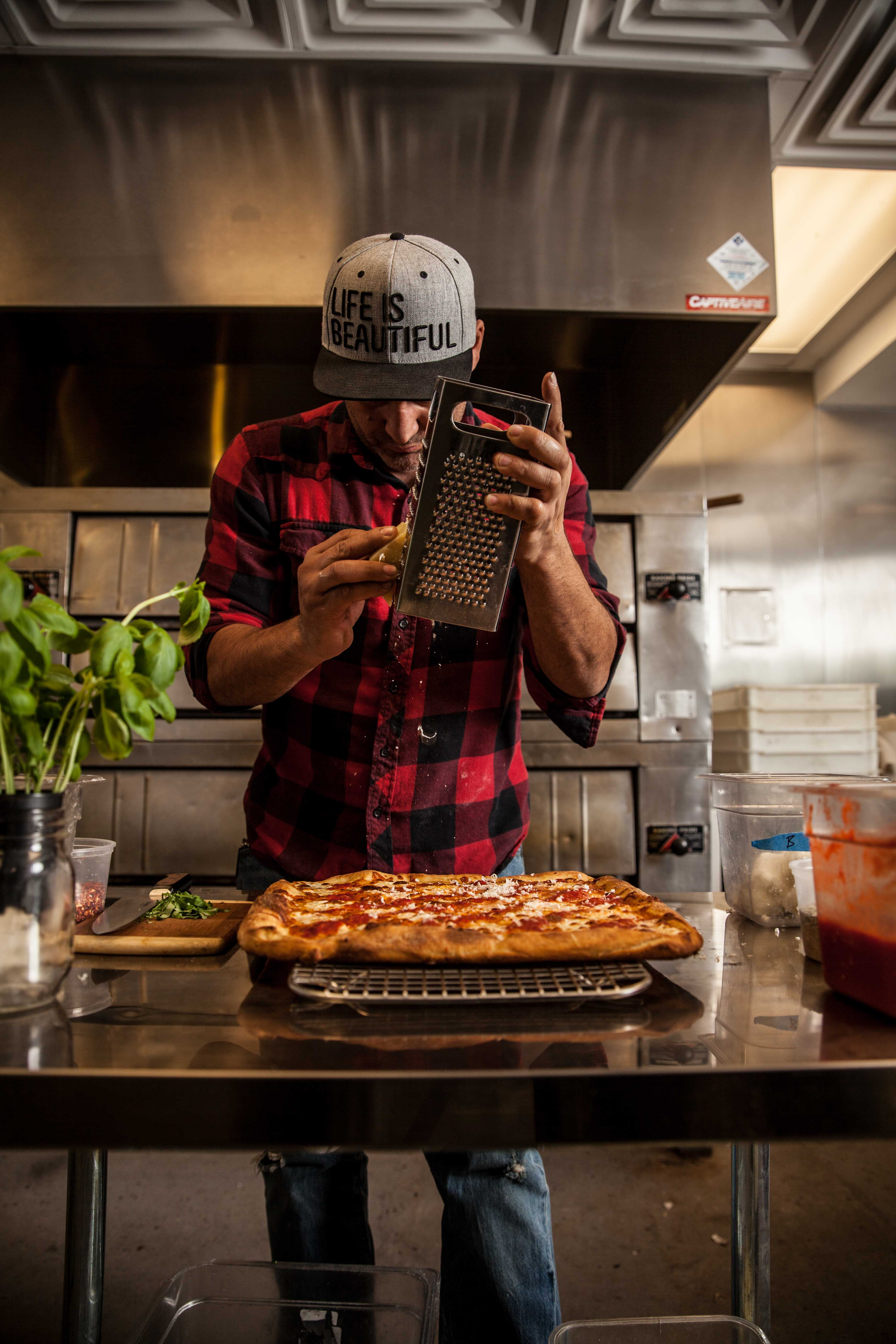 A man in a red plaid button-down shirt shaves Parmesan on a pizza