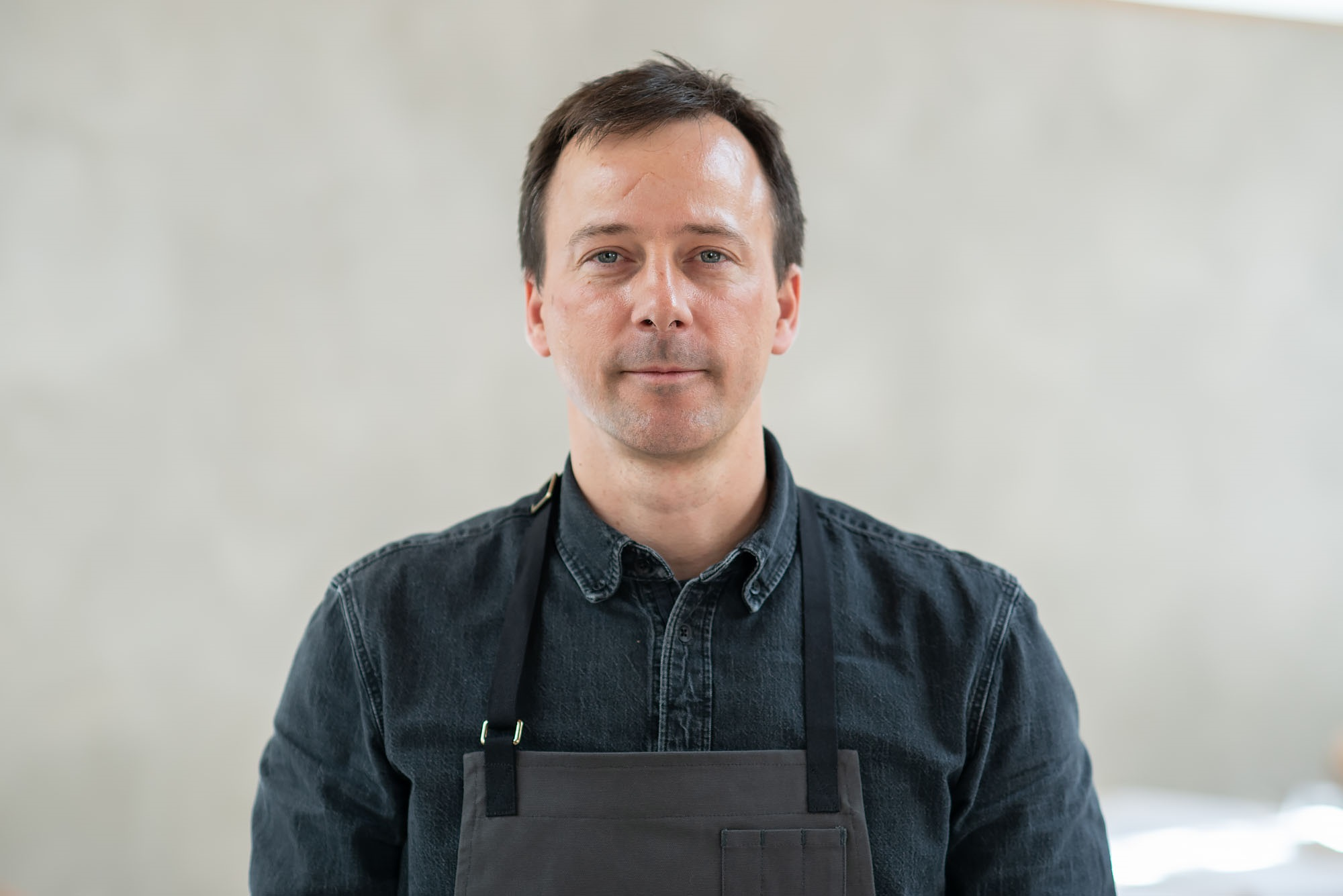 Close up profile shot of Eric Bost wearing dark chef's coat and apron.