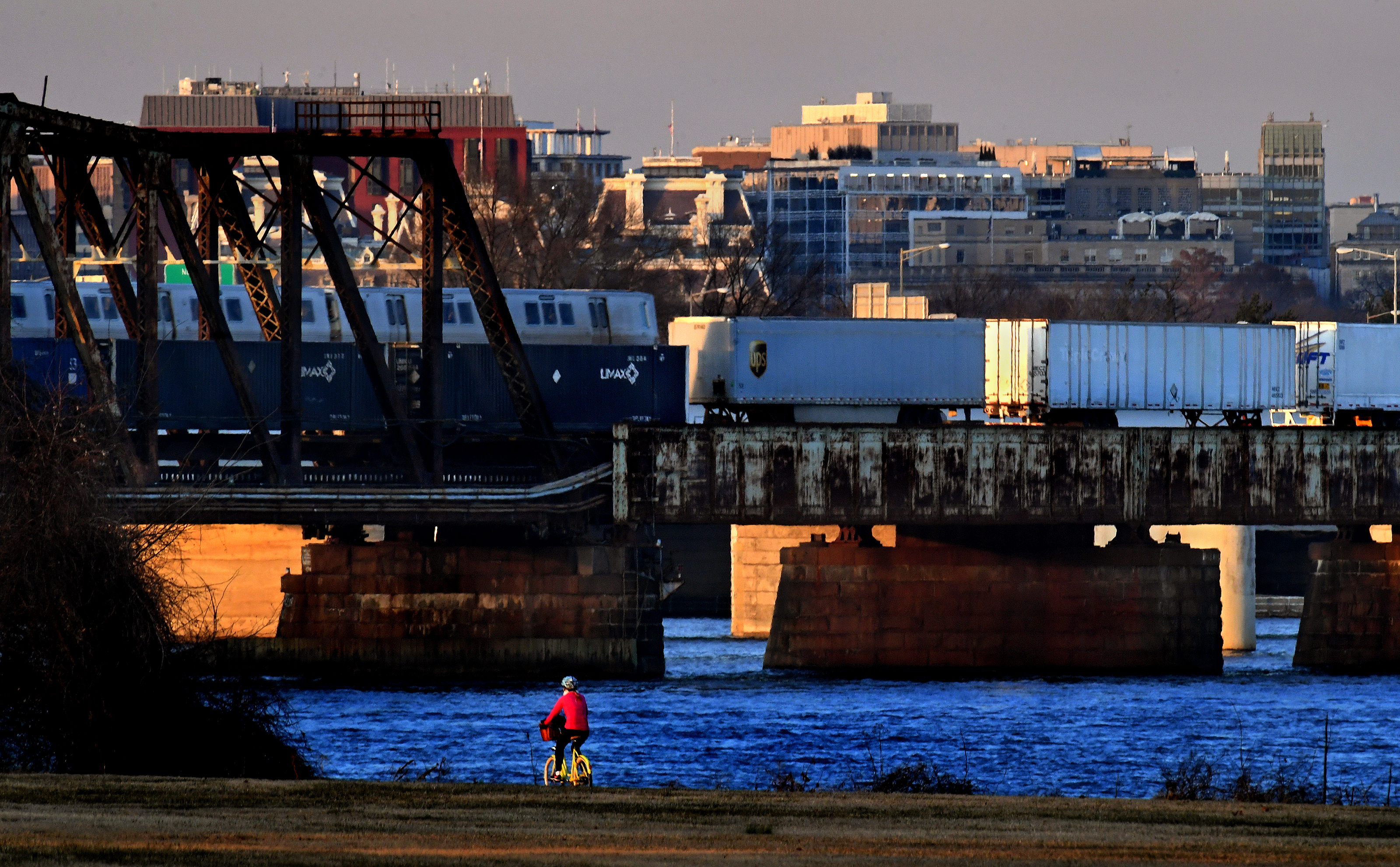 A freight train crosses a bridge over a river. A person rides a bicycle in the foreground and there are tall building sin the background.