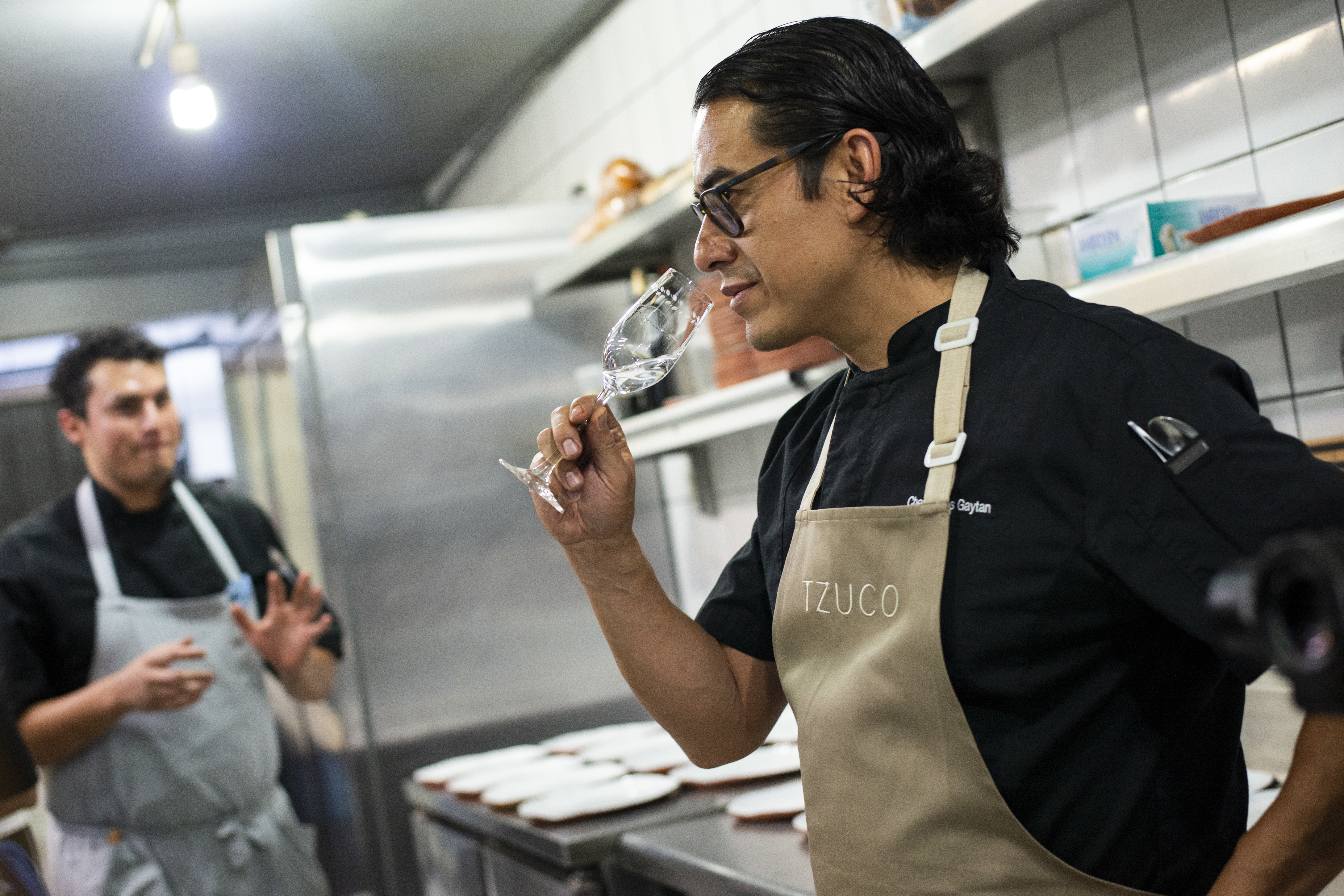 A chef drinking wine in a kitchen.