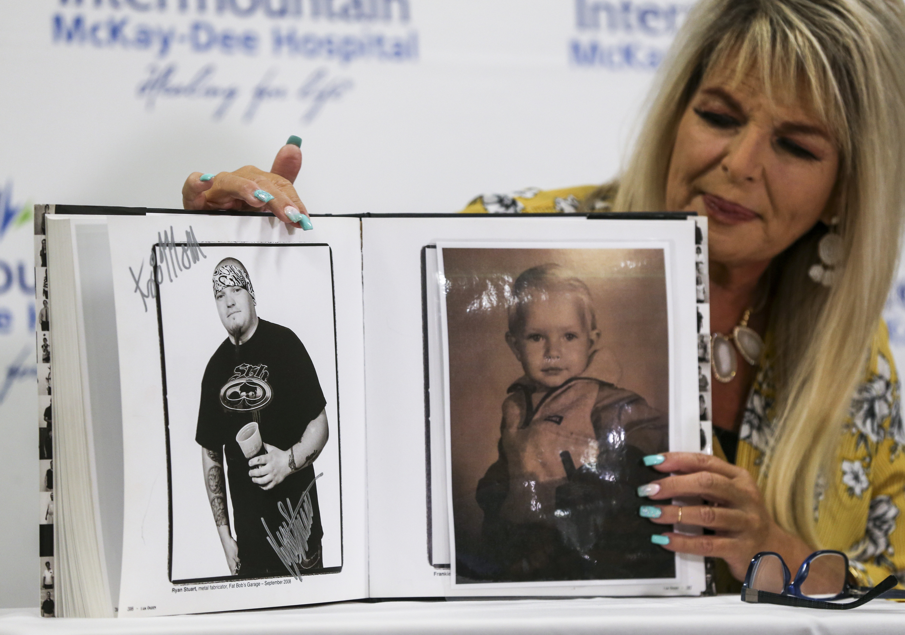 Gina Vodopich looks at photos of her son, Ryan Stuart, during a press conference called for the first case of West Nile virus in Weber County this year at the Intermountain McKay-Dee Hospital in Ogden on Tuesday, Sept. 10, 2019. Stuart has been in the hospital for nine days, most of those spent in the ICU, but was moved out of intensive care recently. He isn't expected to return home until after the New Year.