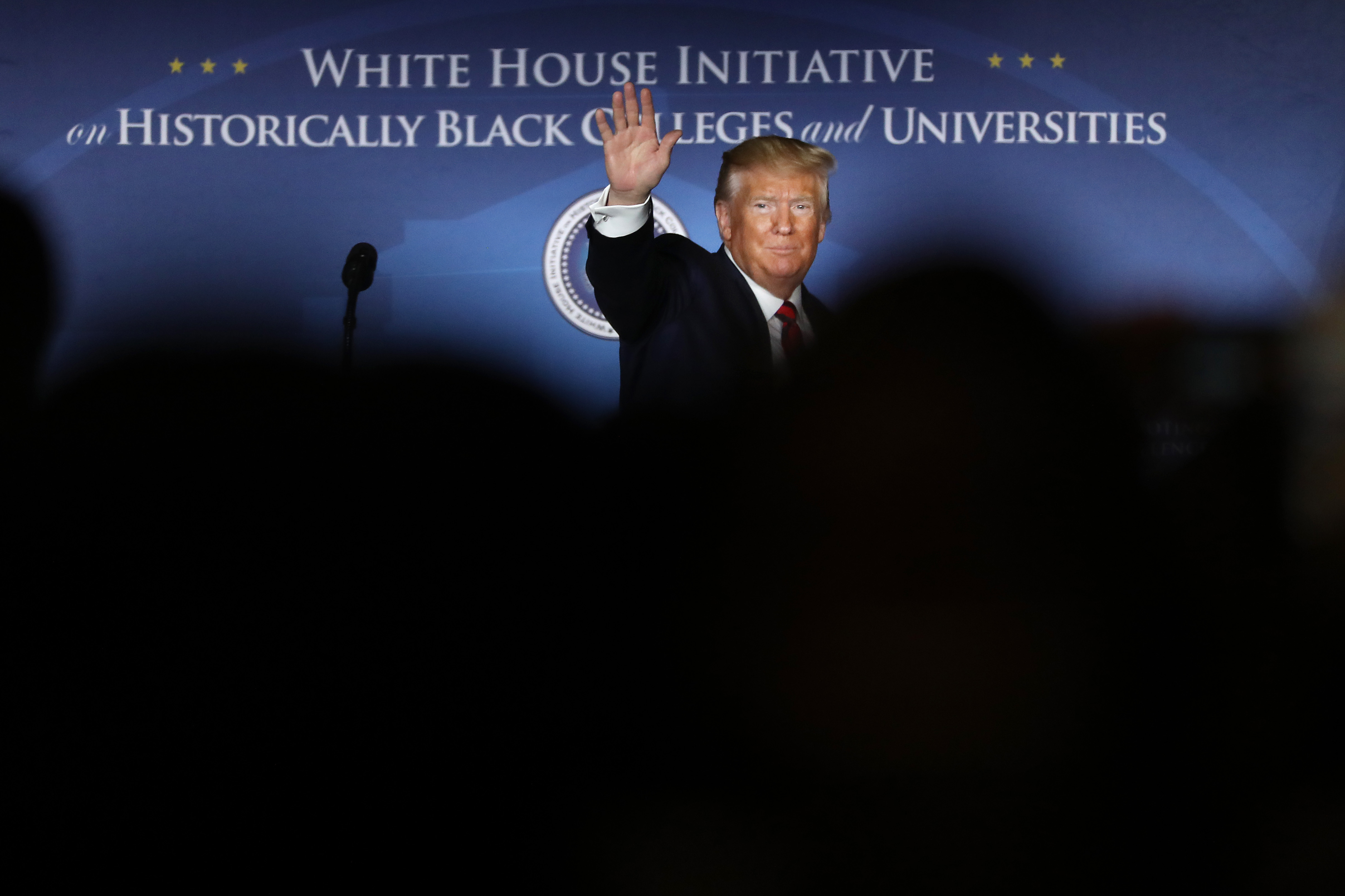 """President Donald Trump waves from the stage in front of a backdrop the reads, """"White House Initiative: Historically Black Colleges and Universities."""""""