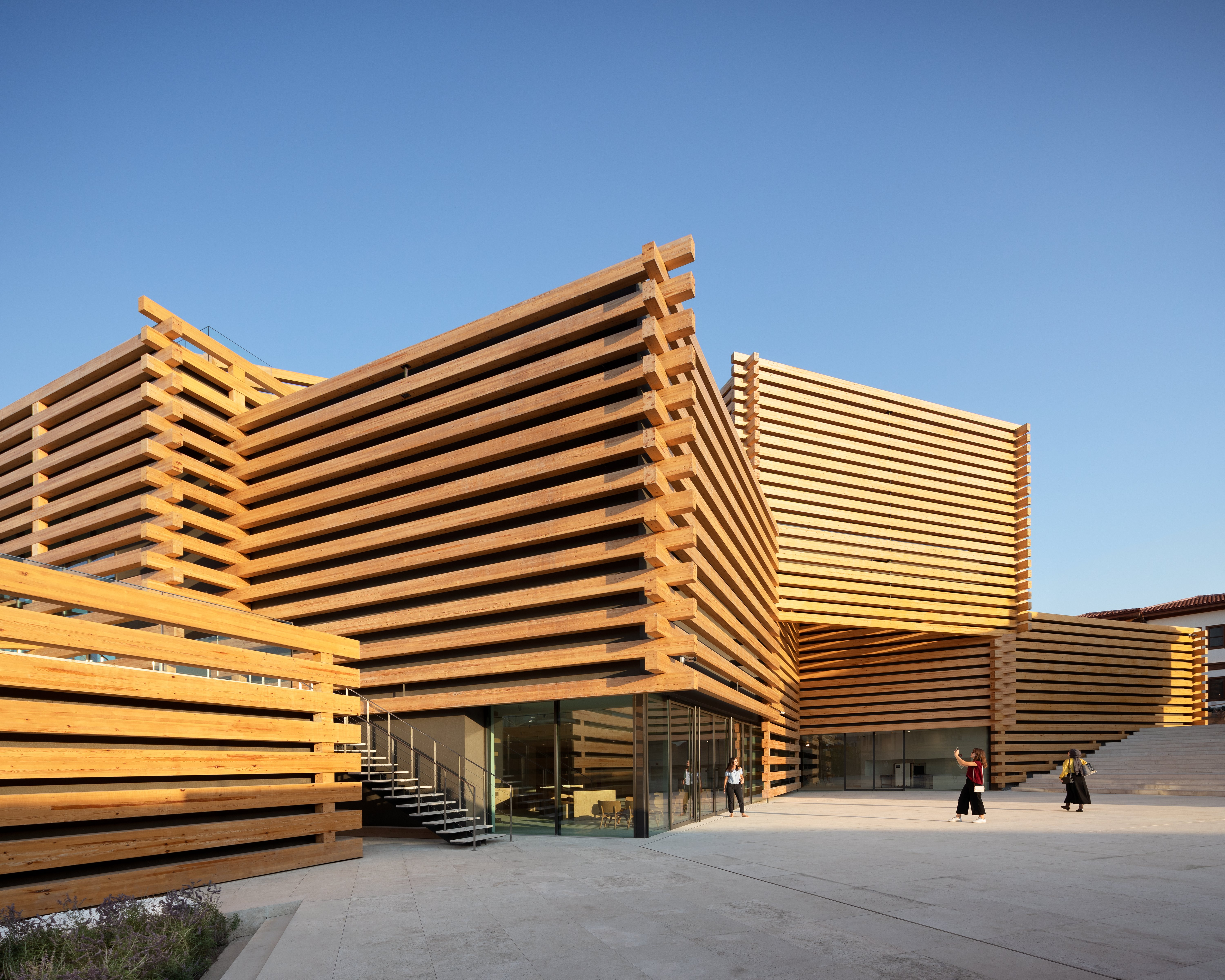 A large golden building made from intersecting wooden volumes. each looking like stacked beams.