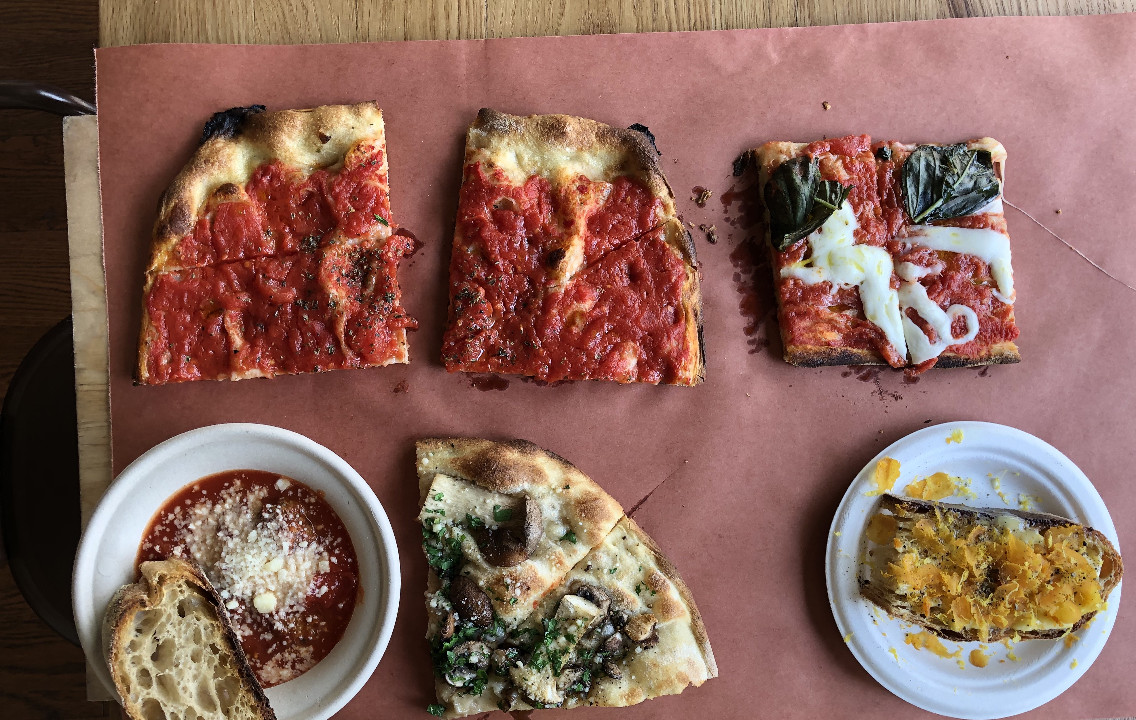 A spread of dishes, including tomato pizza, margherita pizza, meatballs, and bottarga toast, sits on a sheet of red butcher's paper at Bread & Salt in Jersey City