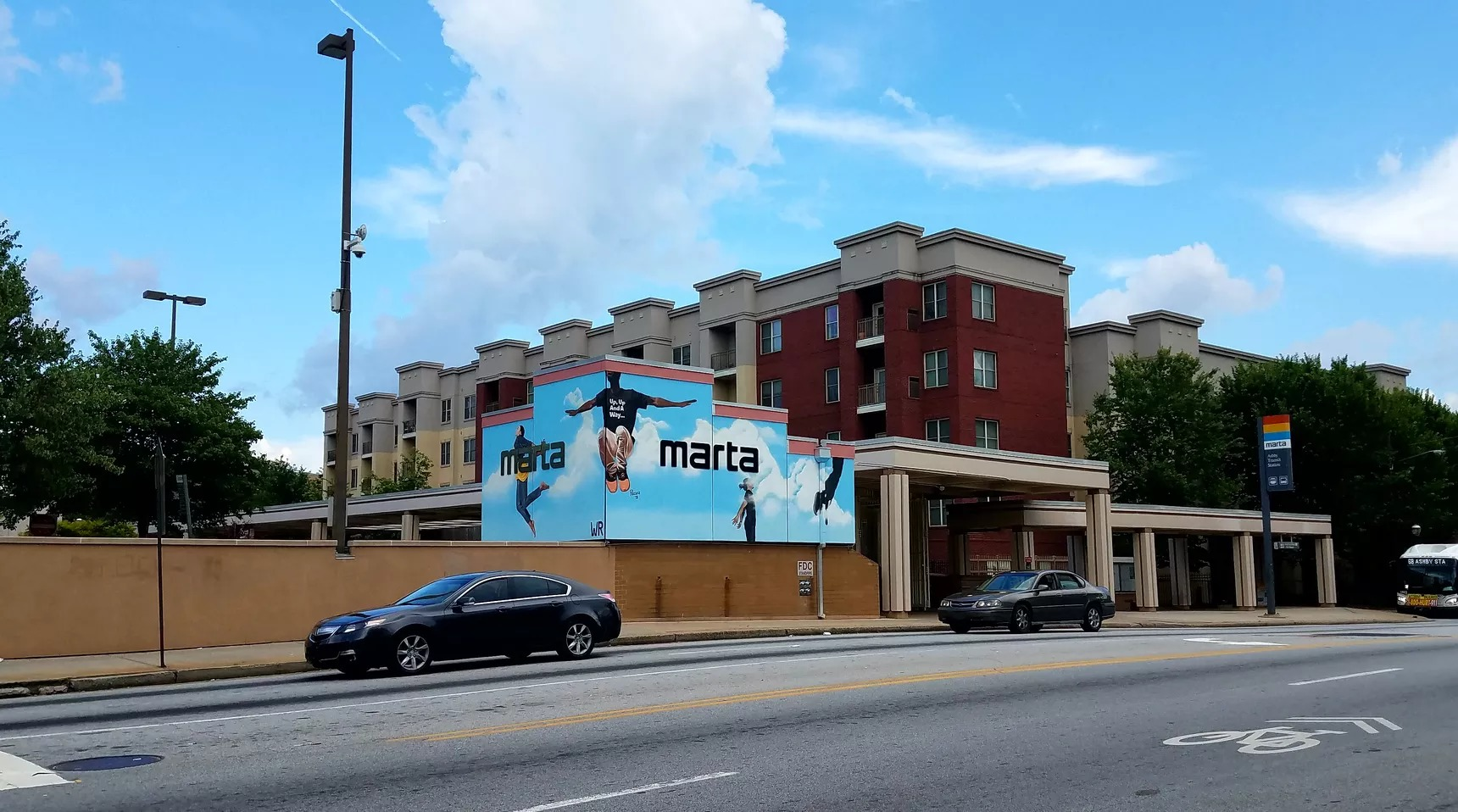 A bright blue mural is painted on the side of the Ashby MARTA station.