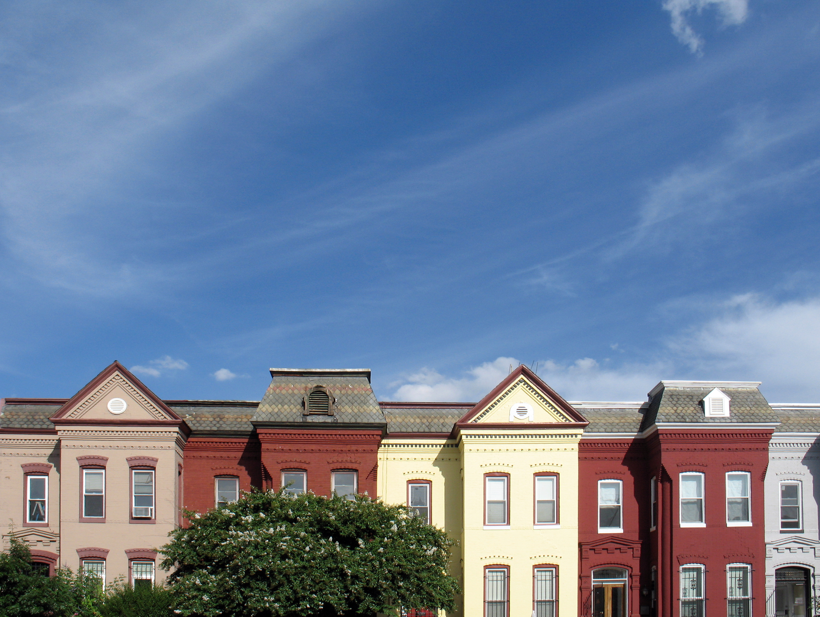Several rowhouses of various colors in Washington, D.C., under blue skies.