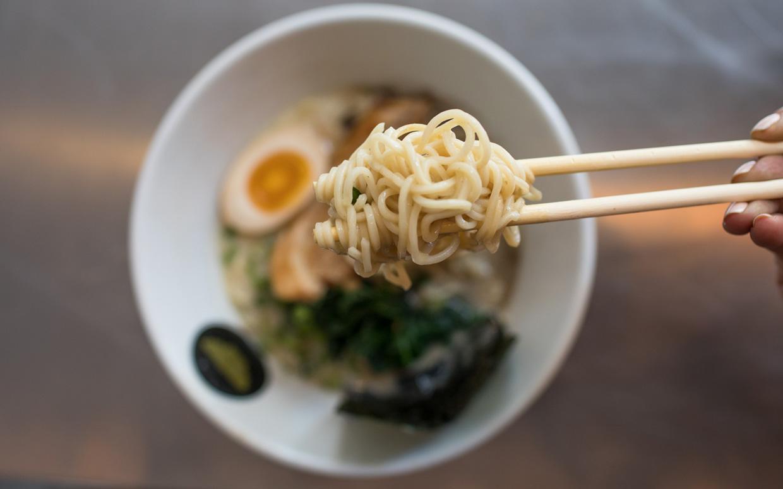 Ramen noodles on chopsticks above a bowl of ramen